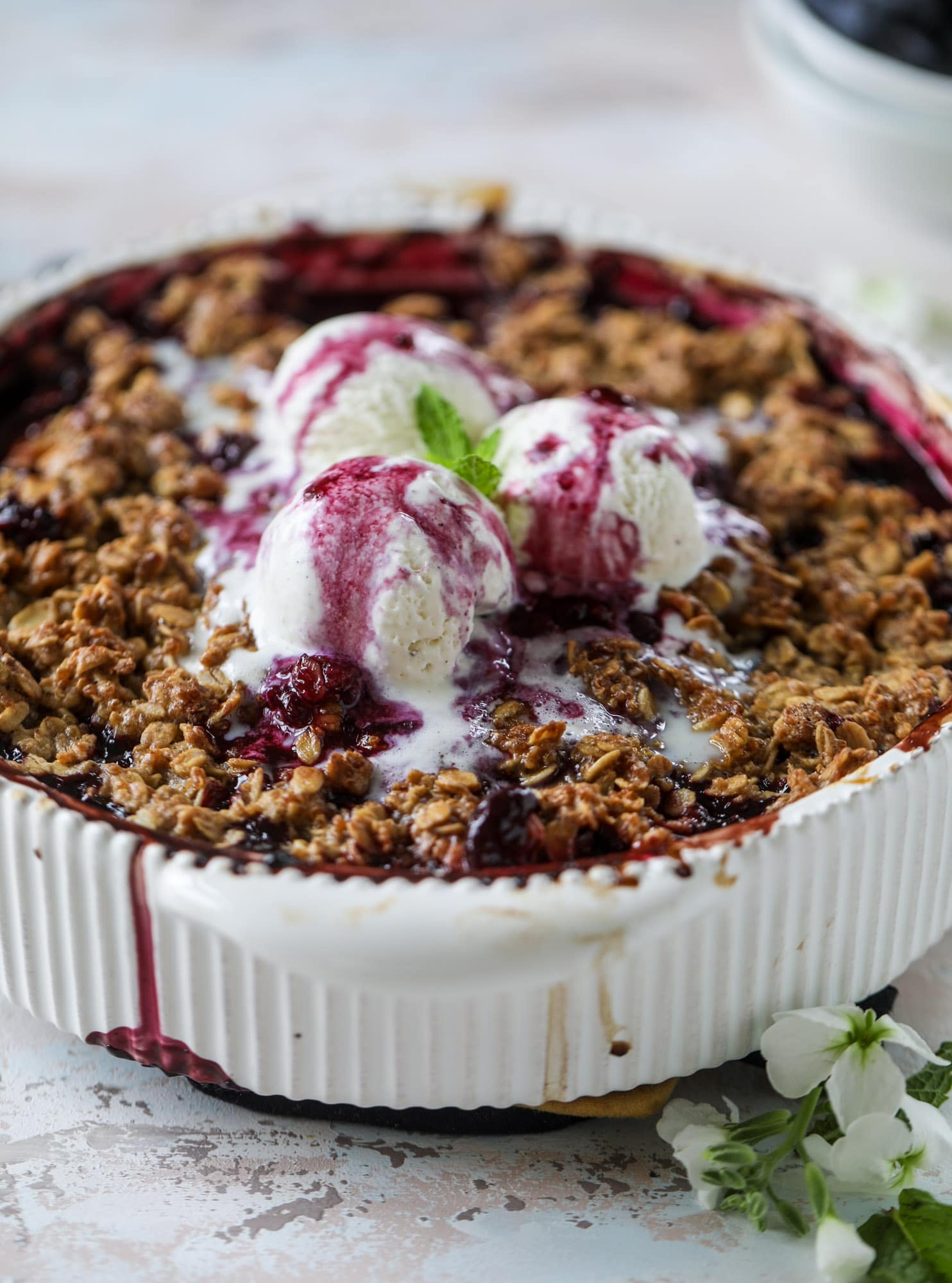 This blueberry crisp is warm and bursting with sweet and juicy fruit. It's topped with a quinoa oatmeal brown sugar topping and is the perfect dessert for summer. Served warm and topped with vanilla ice cream, it's just divine! I howsweeteats.com #blueberry #crisp #quinoa #oats #dessert #fruit