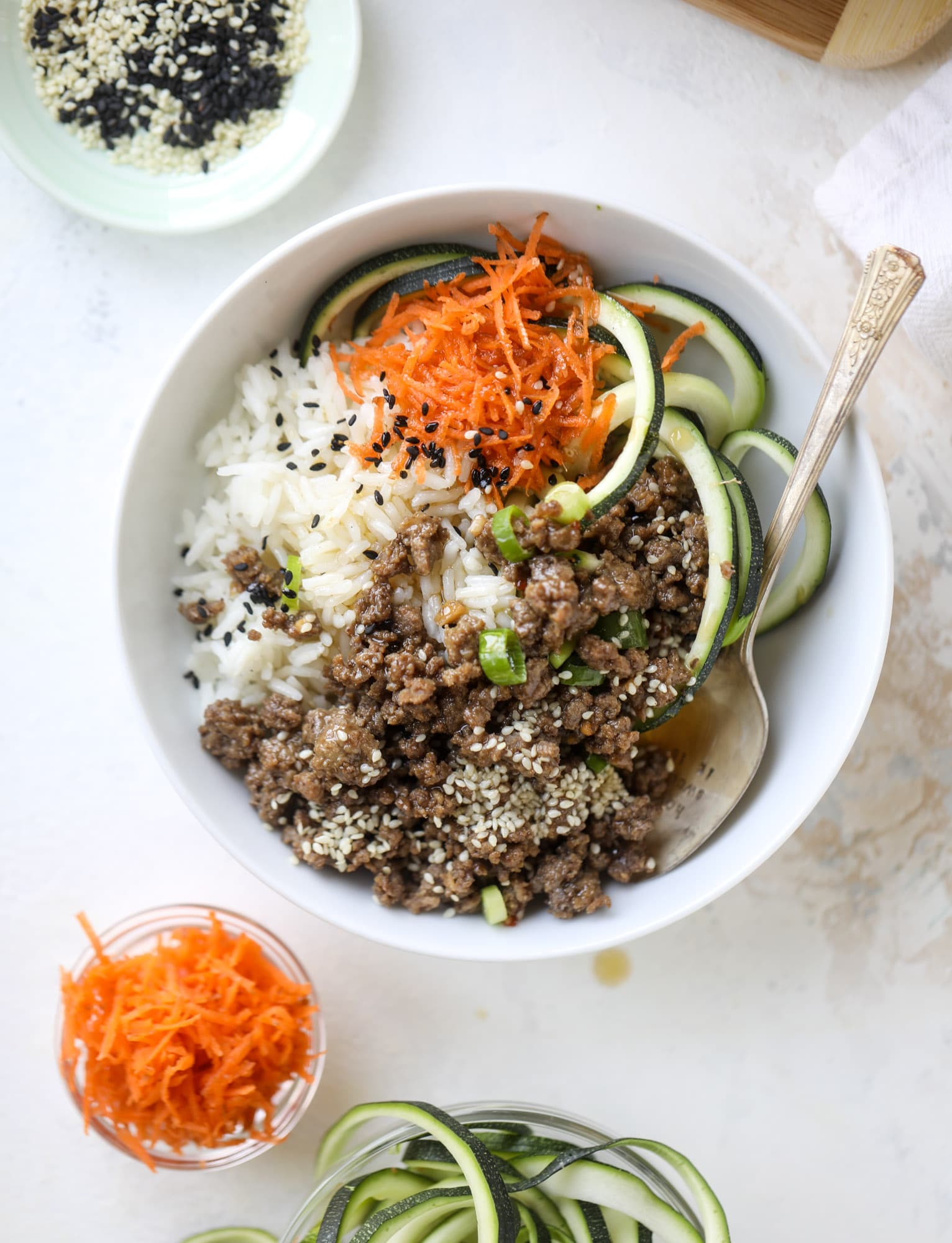 These korean beef bowls are so packed full of flavor that you won't want to eat anything else! Serve the beef with zucchini noodles, grated carrot and jasmine rice for a satisfying, flavor-packed bowl that comes together easily and quick! I howsweeteats.com #korean #beef