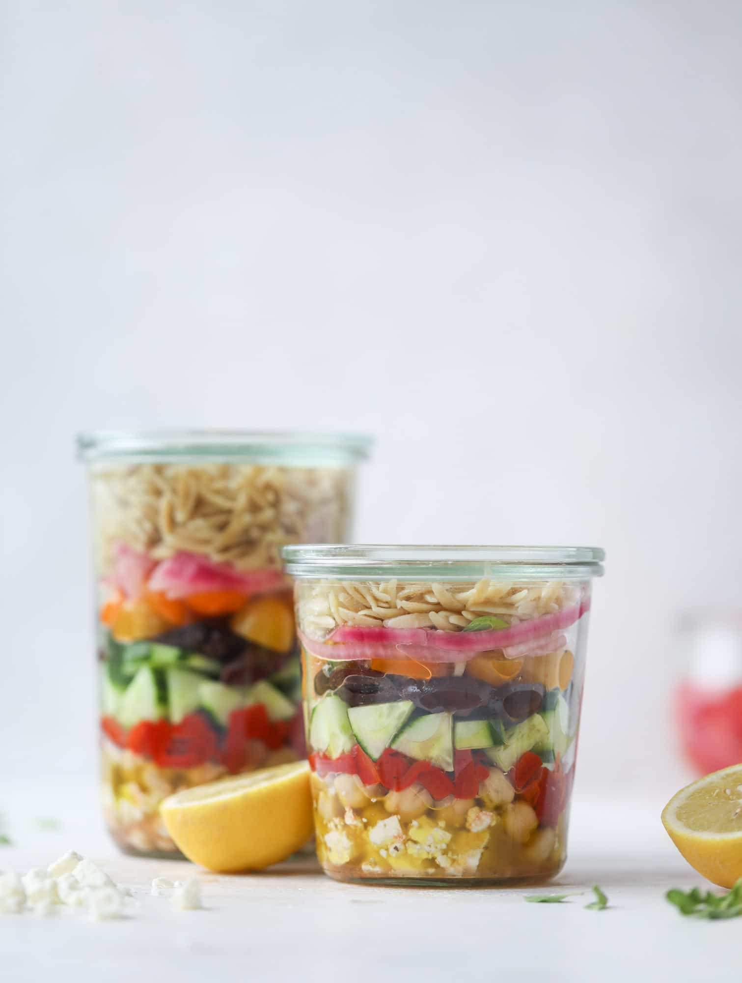 This incredible Greek Orzo salad in a glass is just heavenly! The recipe is so simple and tasty, super satisfying and perfect for preparing meals. This salad in a glass is a delicious lunch idea for the weekdays and keeps you full and happy! I howsweeteats.com #salad #jar #greek #orzo #recipes #healthy #lunch #mealprep