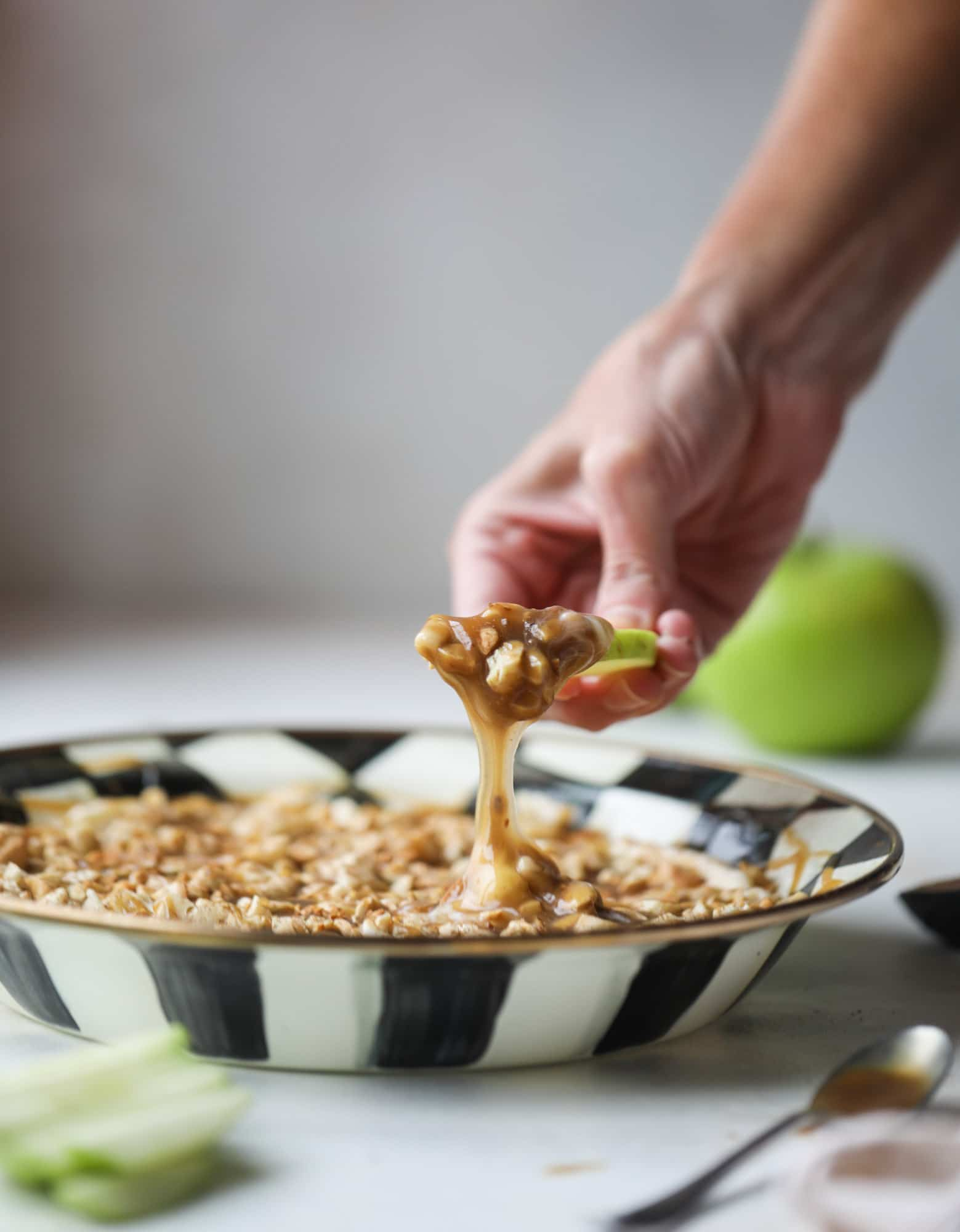 This caramel apple dip is my take on the old-school cream cheese based dip that is super delicious! Here, we have a mascarpone base with a bourbon caramel sauce, topped with roasted chopped cashews. Just add apples! I howsweeteats.com #caramel #apple #dip #appetizer #snack