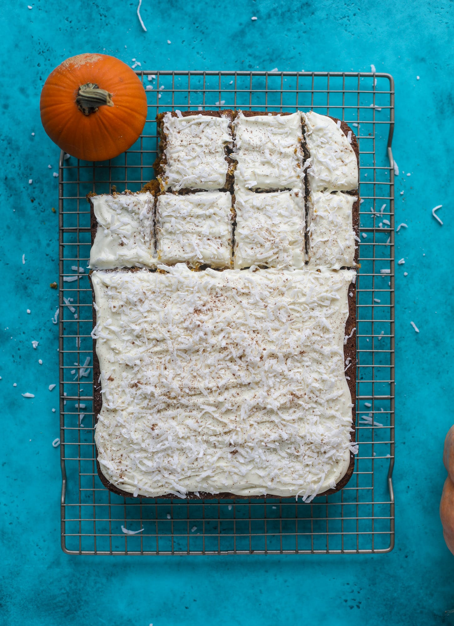 This pumpkin coconut cake is super tender and delicious and comes together quickly in a baking dish! It's spiced for the season and covered in a fluffy coconut cream cheese frosting. You can made it ahead of time for a crowd and it's a huge hit! I howsweeteats.com #pumpkin #cake