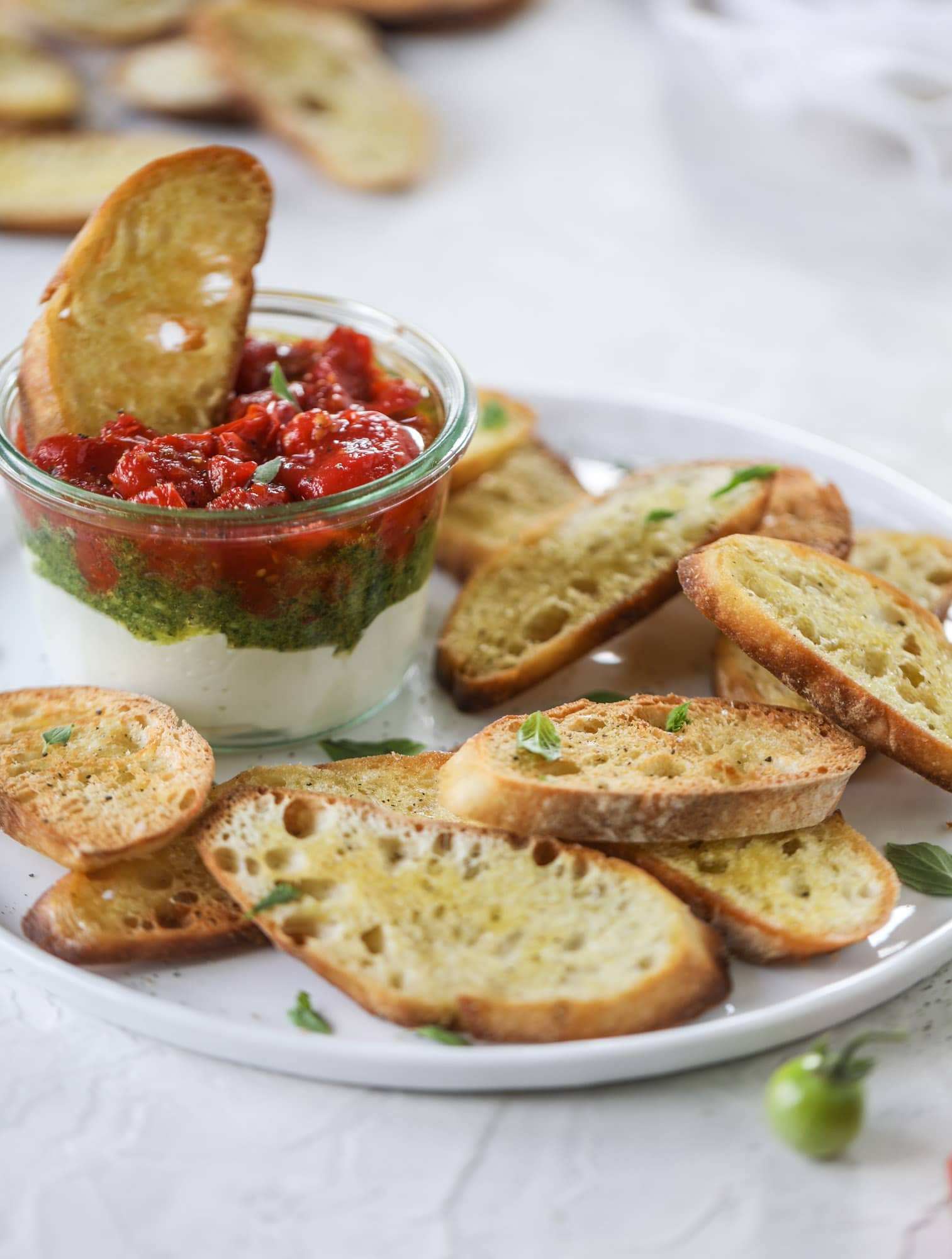 This ricotta jam jar is the perfect appetizer and snack to serve at a party! Based on the ricotta jam jar served at Nordstrom Cafe, it starts with creamy ricotta, is topped with flavorful basil pesto and a quick tomato jam. Serve with crunchy bread and dip dip dip! I howsweeteats.com #ricotta #jam #jar #nordstrom #tomato #pesto #appetizer #dip