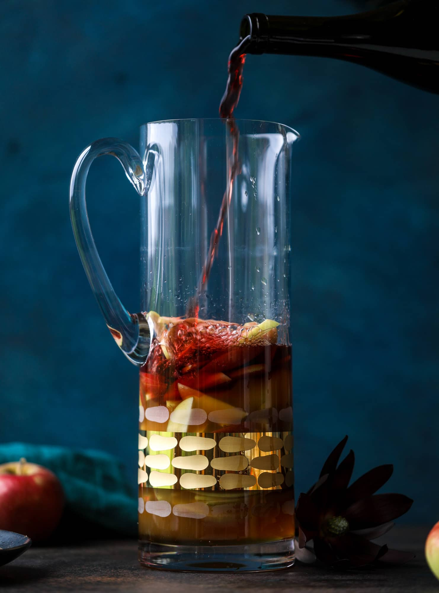 This red apple cider sangria will soon because a staple for your fall! It's delicious and not too sweet, with a base of red wine, apple cider and maple syrup. Cinnamon sticks and apple slices round out the pitcher and it's so flavorful and perfect for the season! I howsweeteats.com #red #apple #cider #sangria