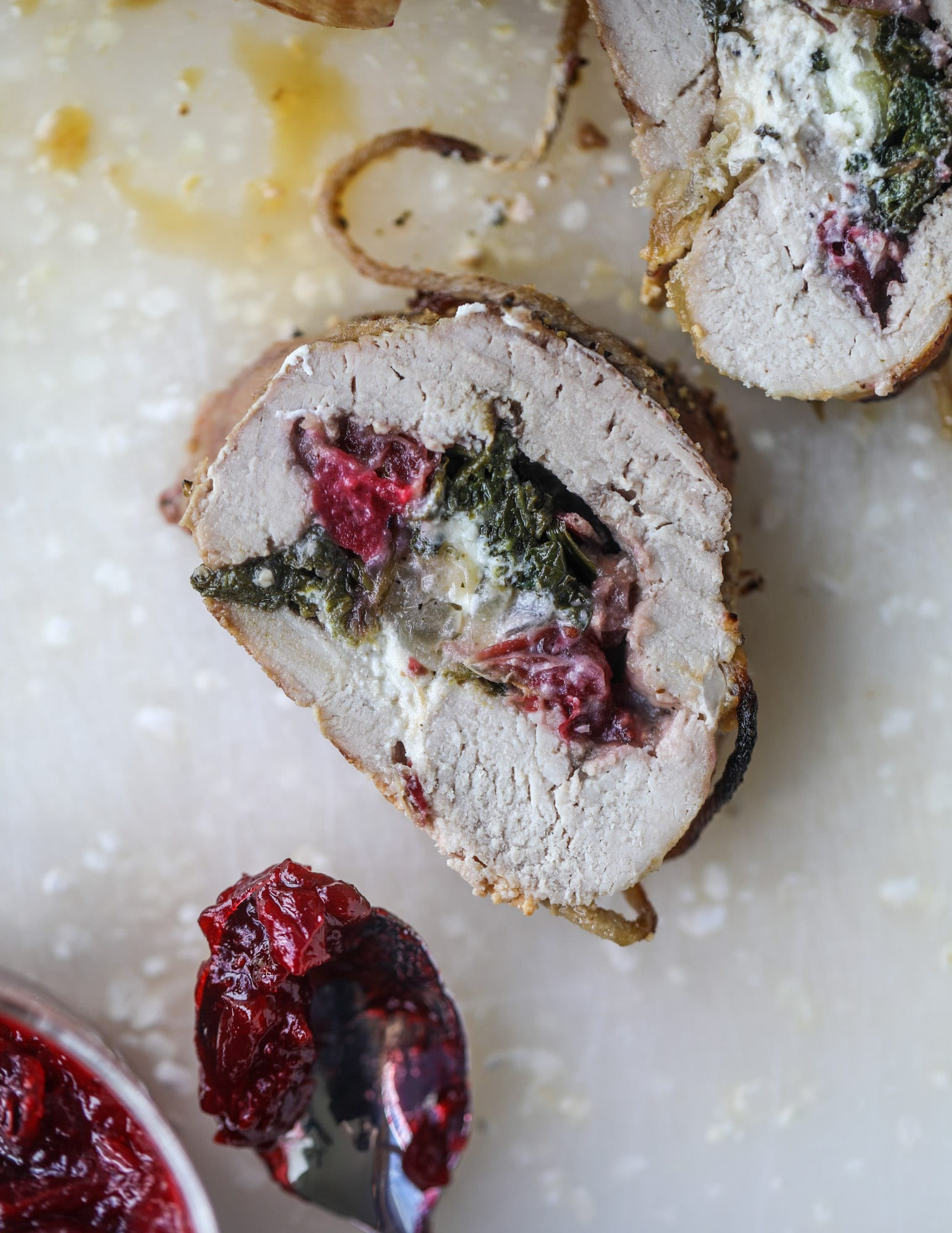 This holiday stuffed pork tenderloin is filled with caramelized onion, fresh cranberry sauce, goat cheese and fresh spinach. It's a show stopped and super delicious, along with being fairly simple to make! I howsweeteats.com #stuffed #porktenderloin