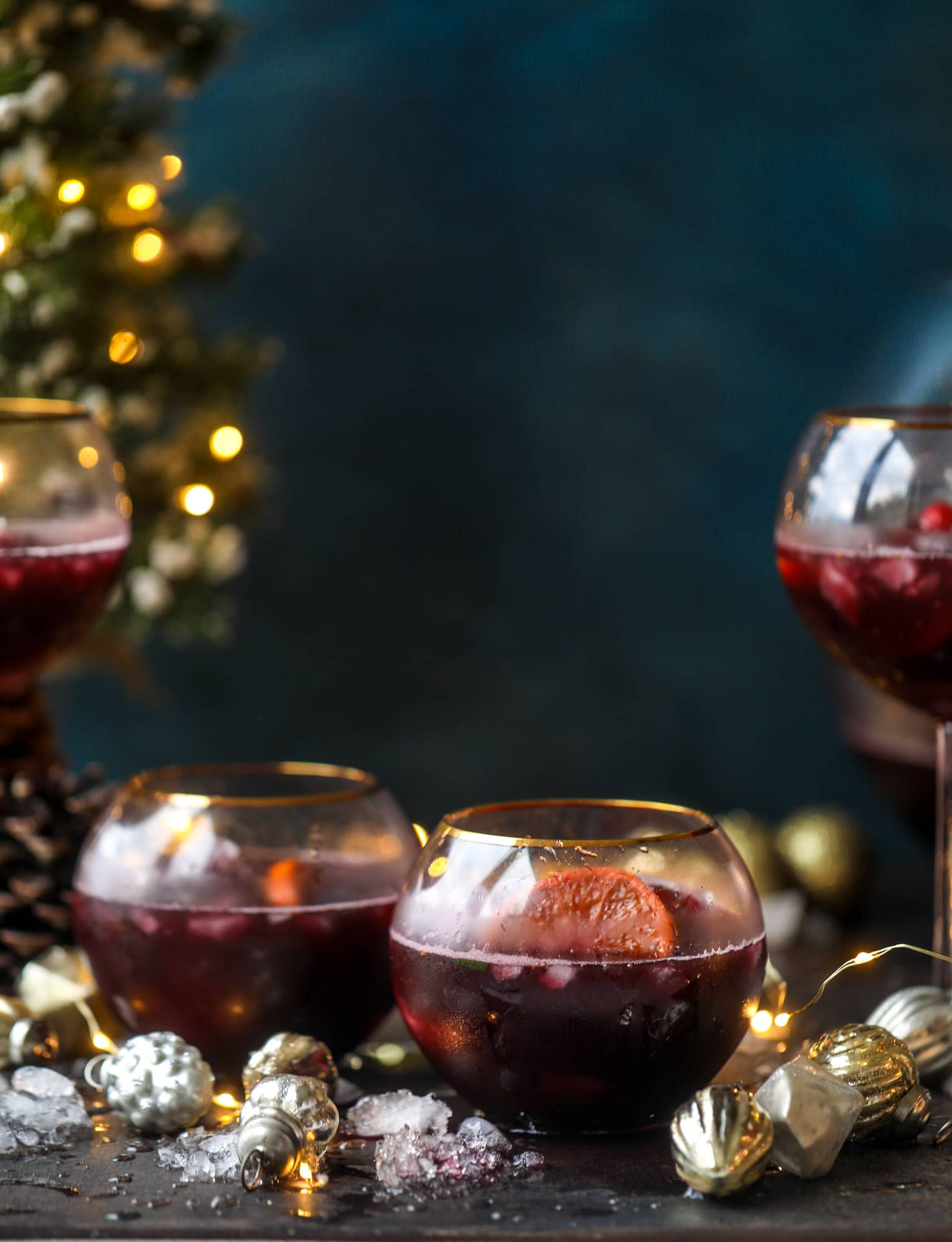 This tree trimming punch is the most perfect christmas punch to drink while decorating the tree! Rich red wine is the base and there's a bit of orange, some spice, cinnamon and a gorgeous jeweled holiday ice cubes! I howsweeteats.com #christmas #punch