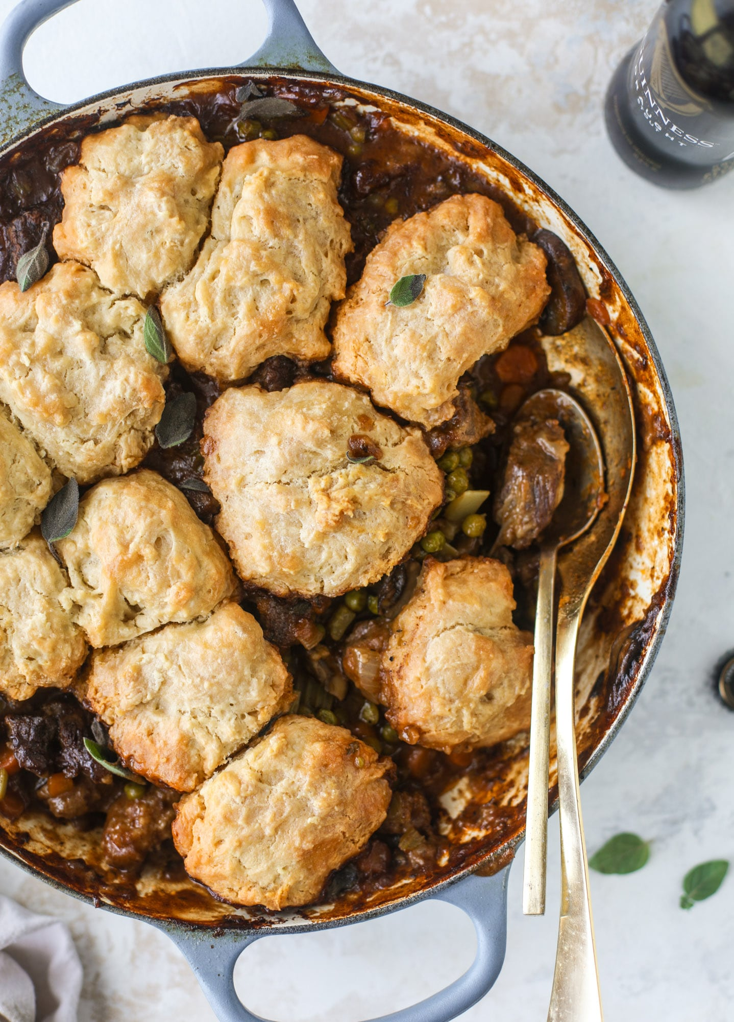 A perfect cold weather comfort food meal, Guiness pot pie has tender, fall-apart beef, lots of vegetables and is topped with buttery beer bread biscuits! I howsweeteats.com #guinness #potpie