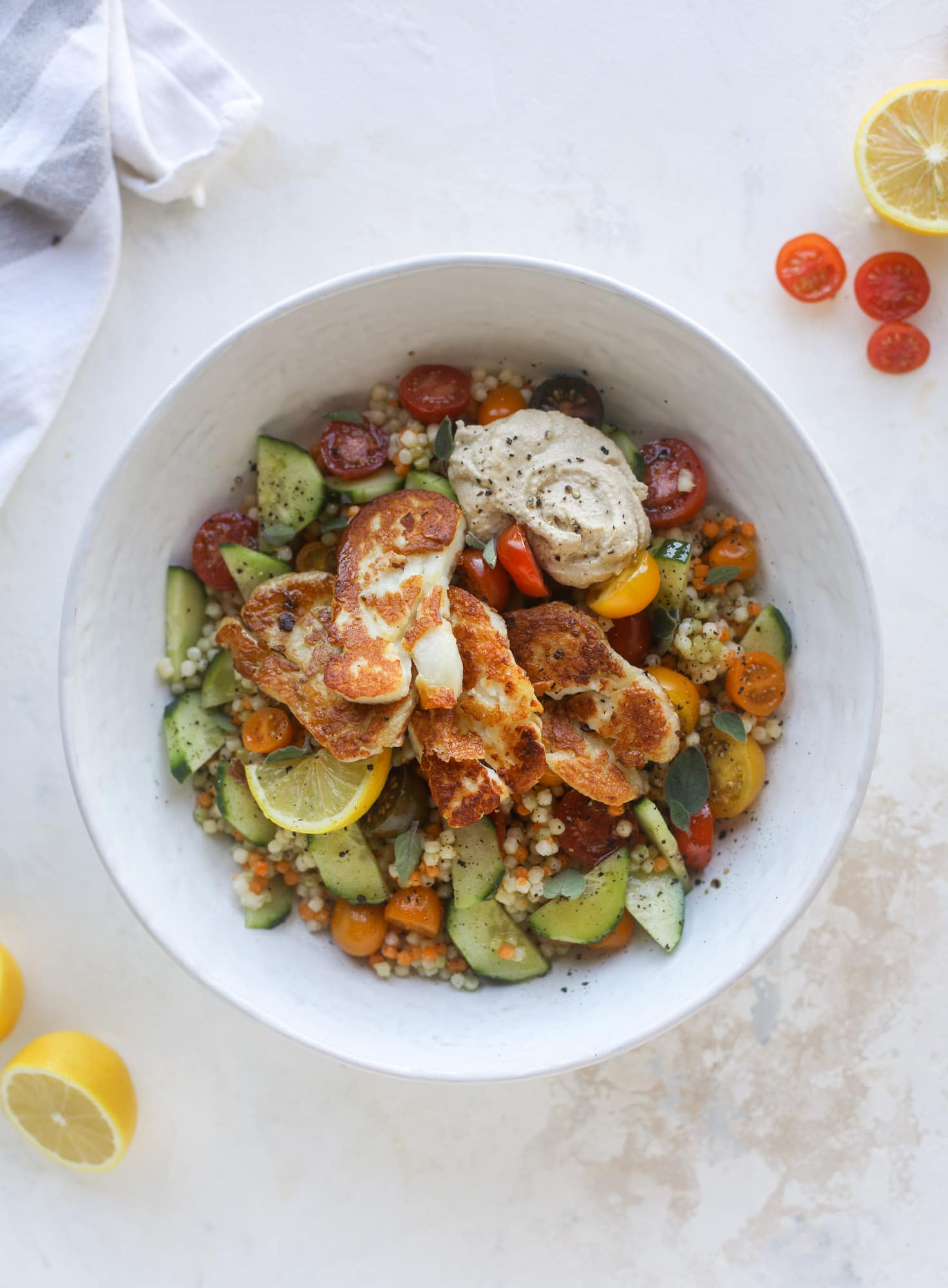 I am obsessed with these haulloumi hummus bowls for lunch or dinner. Couscous, veggies, crispy halloumi cheese and hummus with lots of lemon. Yum! I howsweeteats.com #halloumi #hummus