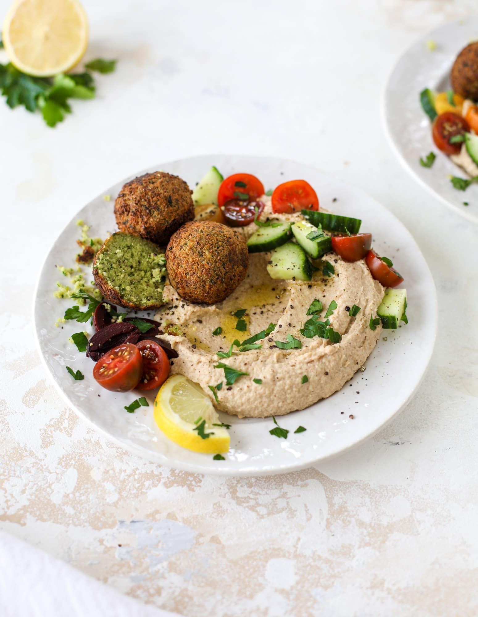 Green goddess falafel is hearty and flavorful, served over the creamiest cauliflower hummus, with tomatoes, olive, cucumbers and feta. Yum! I howsweeteats.com #falafel #cauliflowerhummus