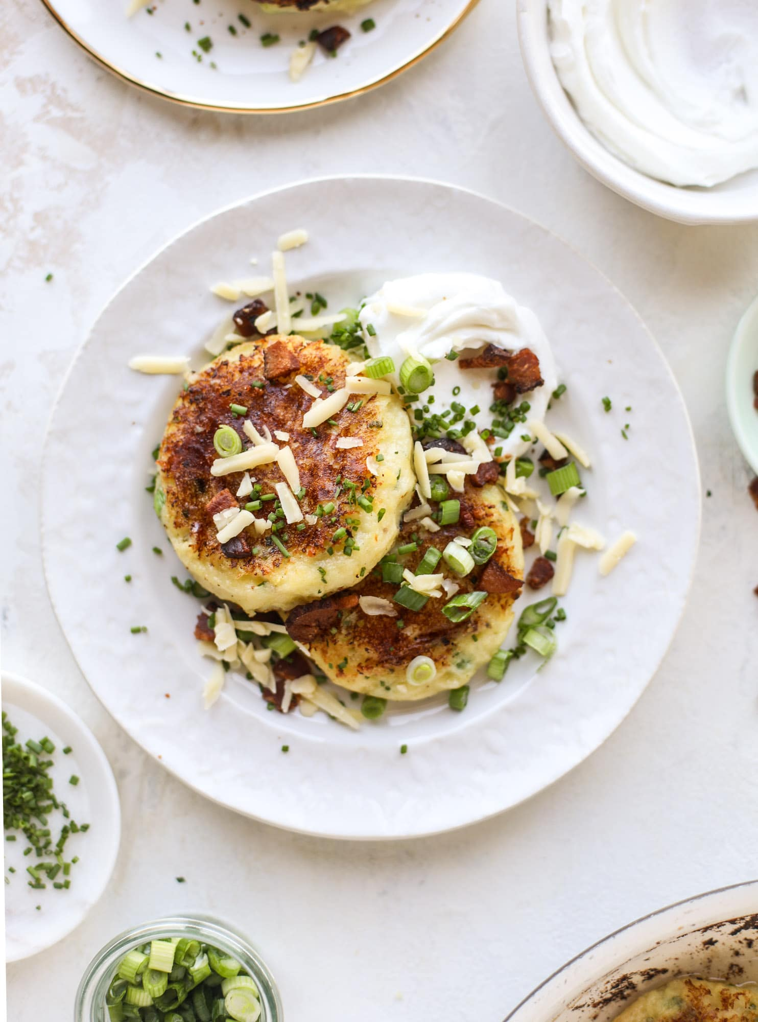 Loaded mashed potato pancakes are the perfect comfort food or side dish to a hearty meat. Crispy mashed potatoes with aged cheddar. Delicious! I howsweeteats.com #mashedpotato #pancakes