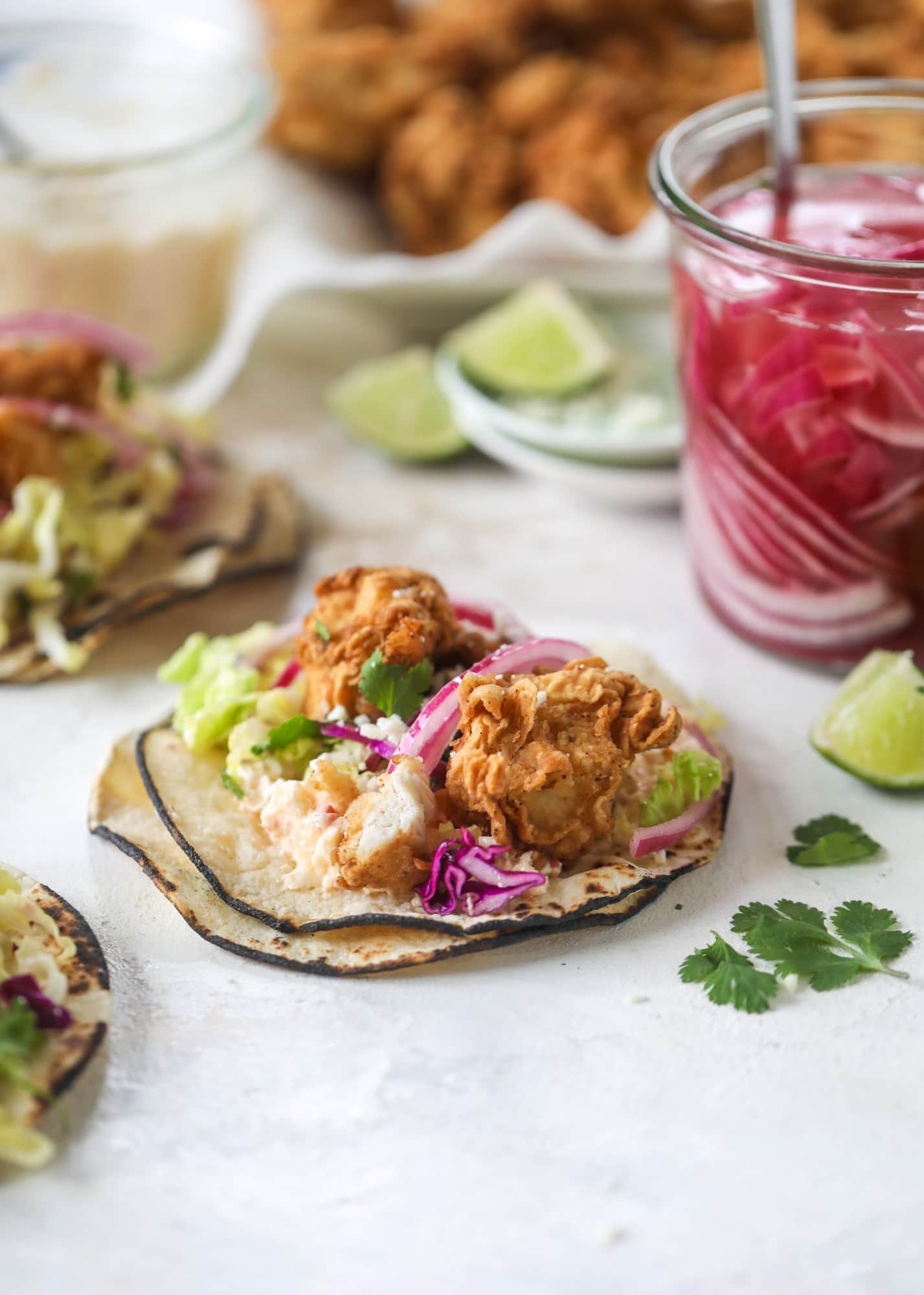 Taking crispy chicken tacos to the next level by wrapping them in a warm tortilla with gouda pimento cheese, lime cabbage and pickled onions!