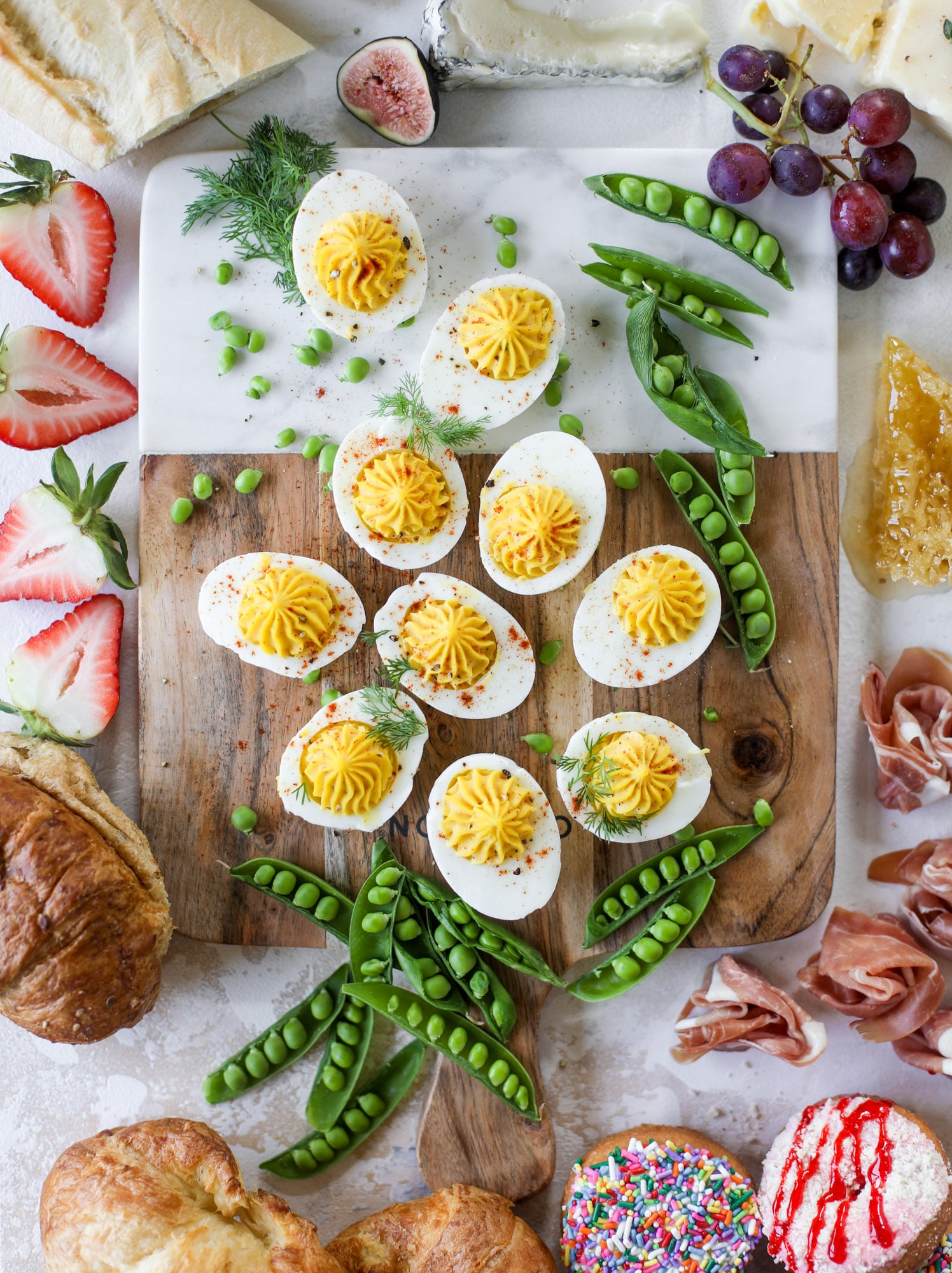 The highlight of this Easter brunch board are the deviled eggs and soft boiled eggs! Add some avocado toast, donuts and bloody marys and you've arrived. I howsweeteats.com #brunch #board