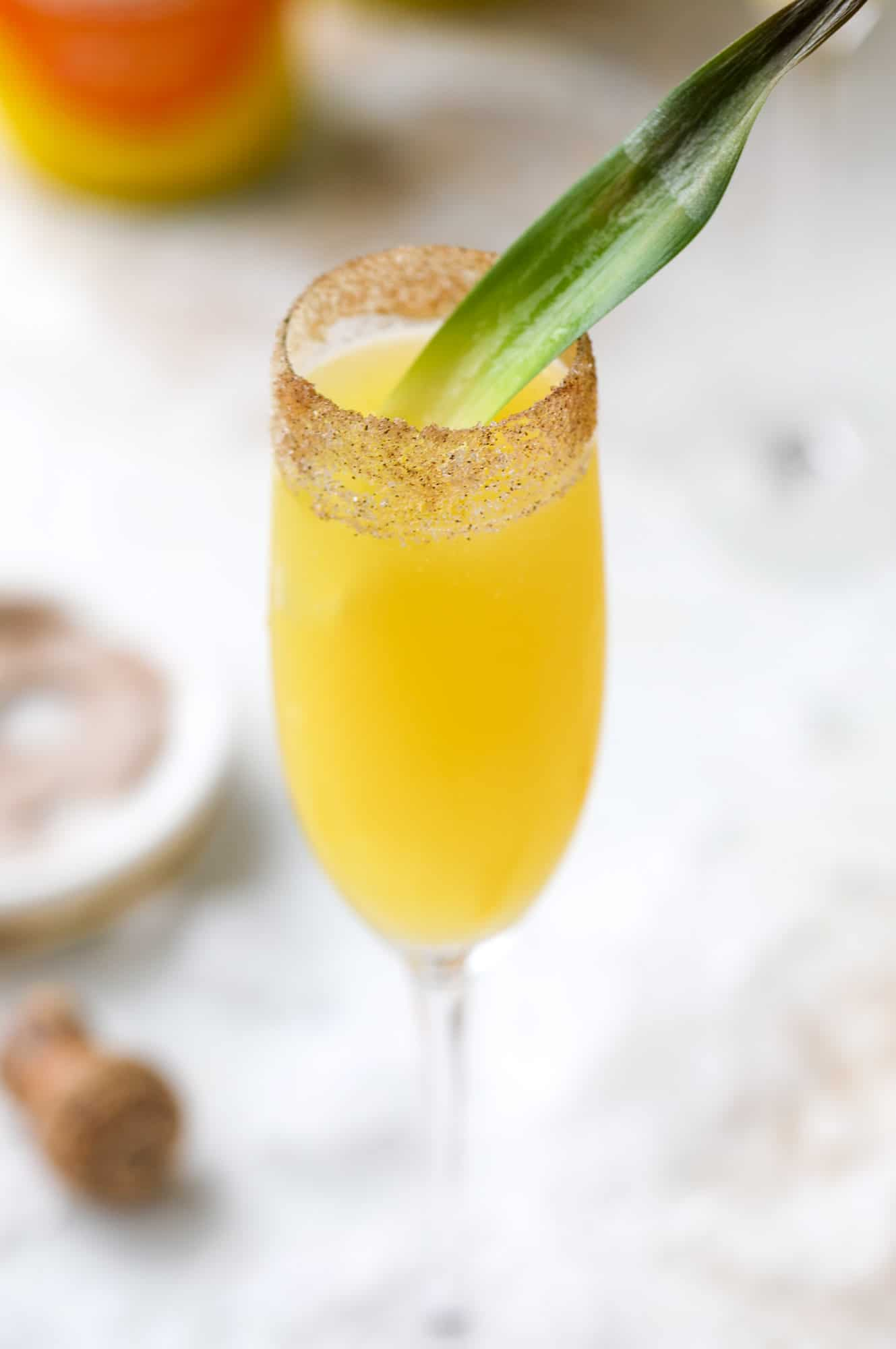 The hummingbird mimosa is a spin on the classic hummingbird cake: pineapple juice, orange juice, champagne and a cinnamon sugar rim! I howsweeteats.com #hummingbird #mimosa