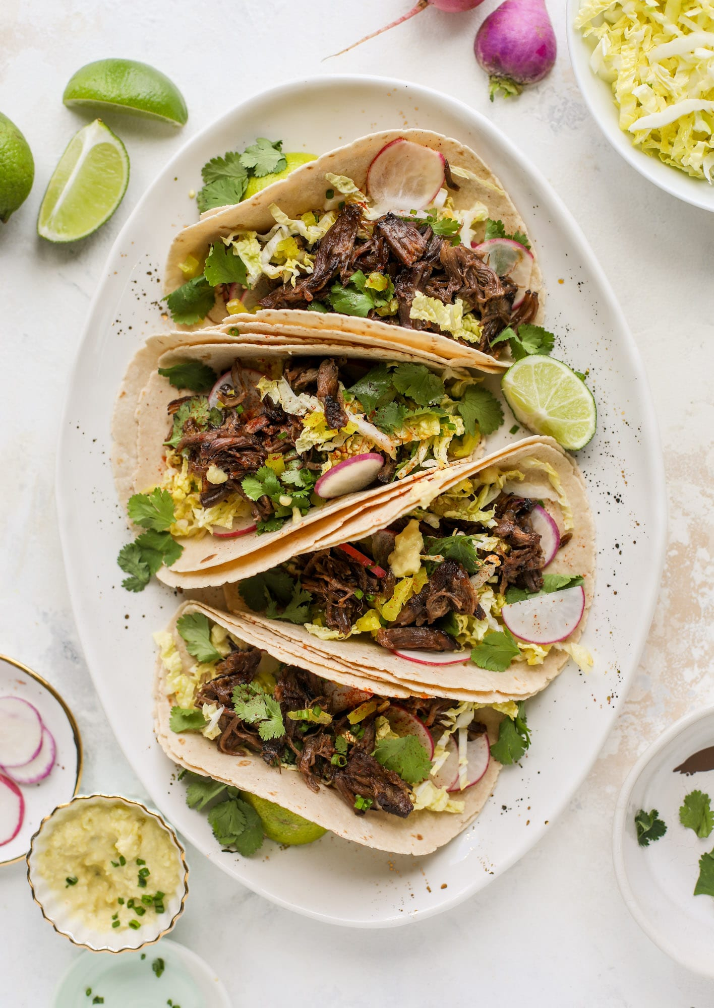 These are the best smoky short rib tacos made in the slow cooker! Served with a banana pepper mustard and napa cabbage slaw, it's a flavor explosion.