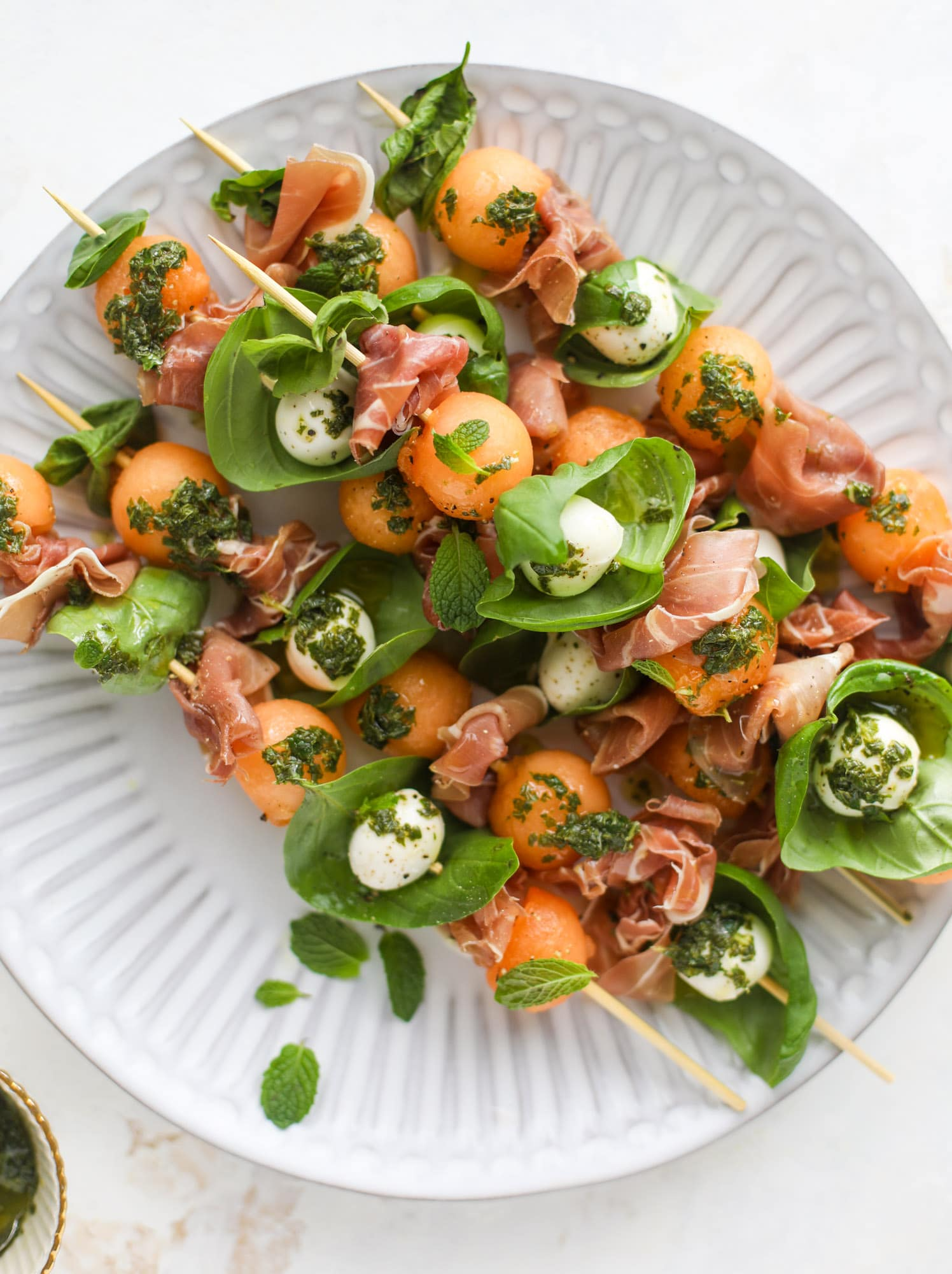 These cantaloupe prosciutto skewers are the perfect cantoloupe caprese snack! Salty prosciutto, sweet melon and fresh mozzarella drizzled with mint pesto!