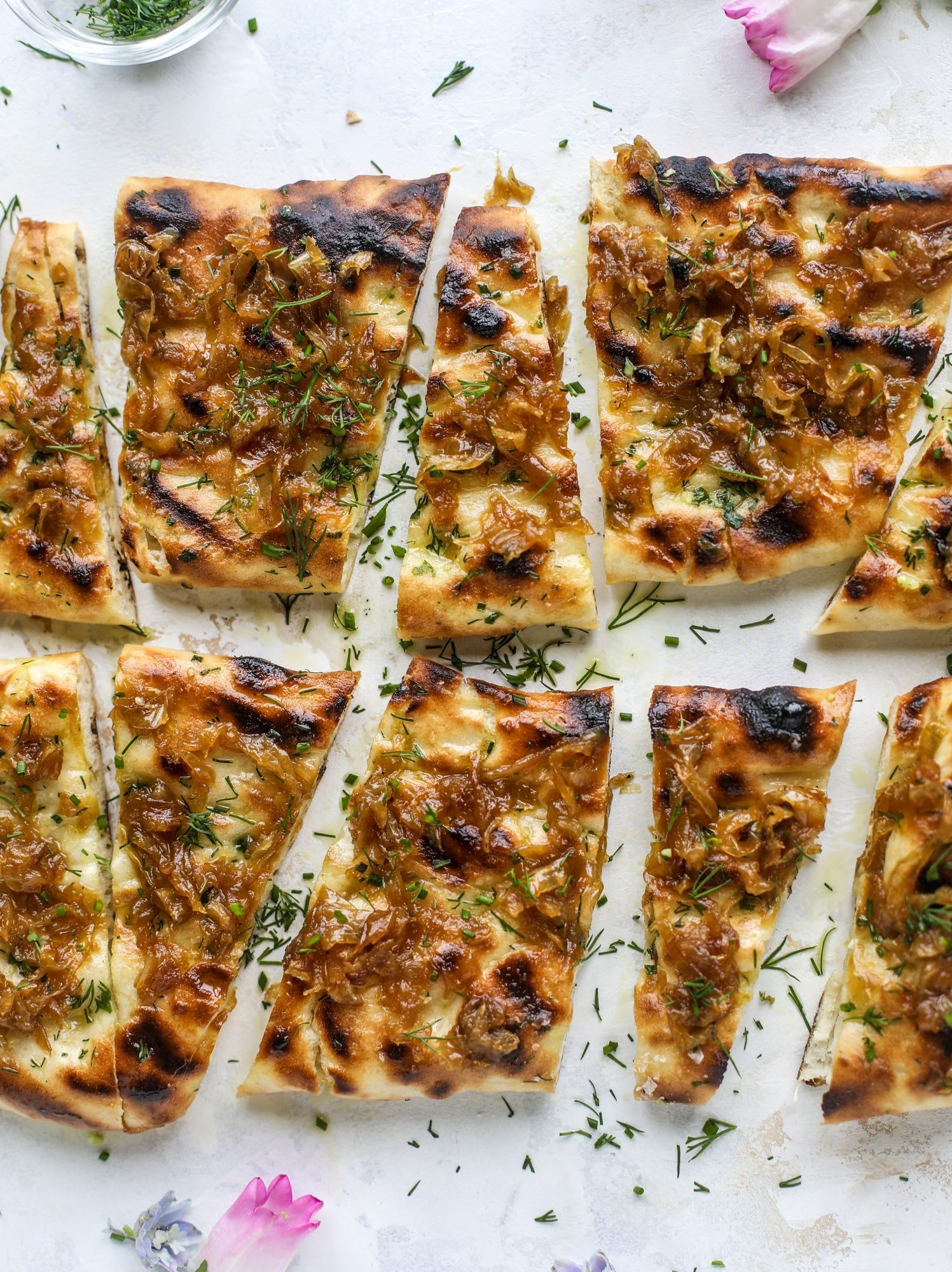 Grilled focaccia bread is such a treat! Topped with puddles of garlic butter, fresh chopped herbs and golden, caramelized onions, it's a slice of heaven.