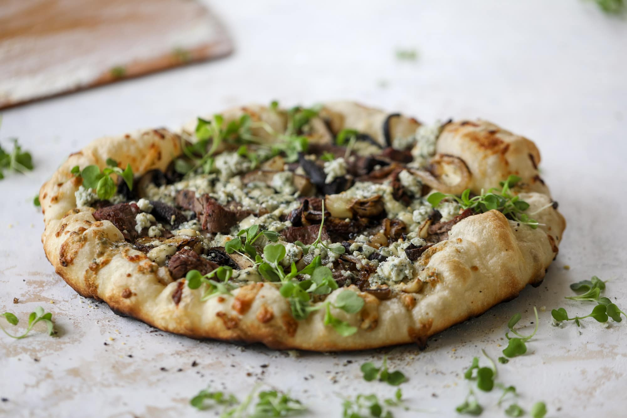 This grilled steakhouse pizza has all the amazing smoky flavors of your favorite steakhouse. Grilled onions, mushrooms and creamy gorgonzola finish it off.