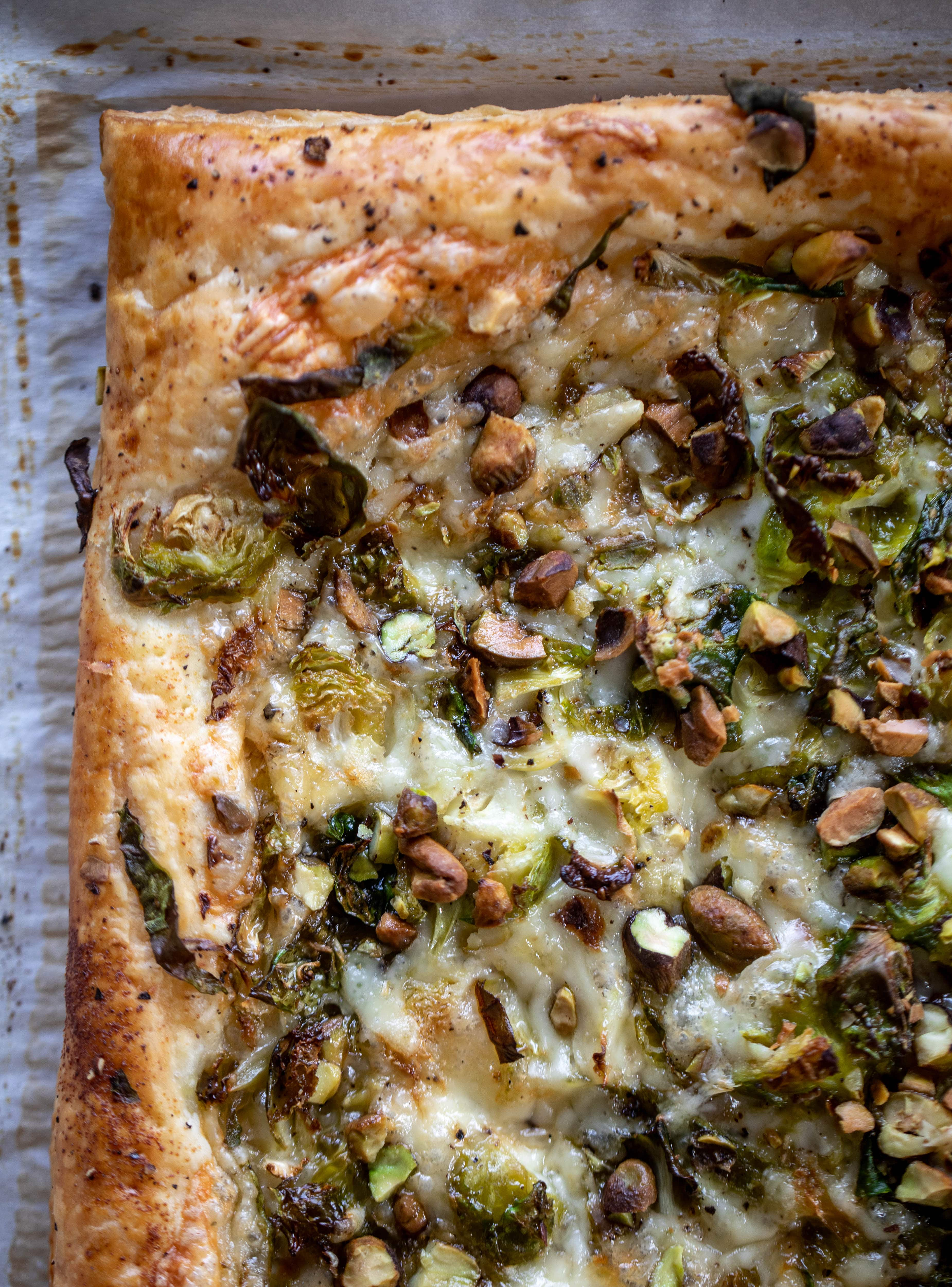 This brussels sprouts tart has a ton of flavor! Melty fontina, sliced brussels and crunchy pistachios all on top of puff pastry. Delish!
