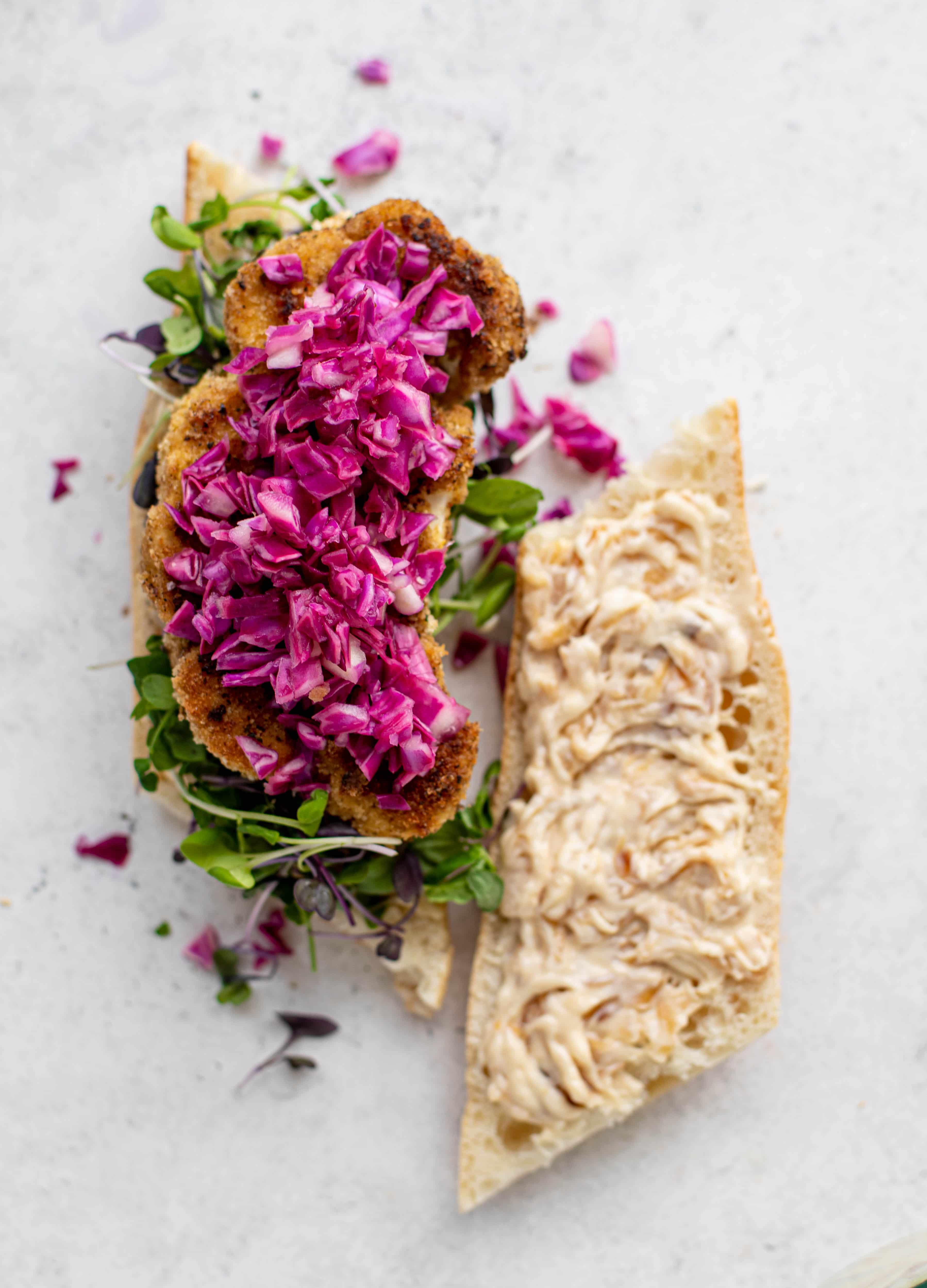 These cauliflower schnitzel sandwiches are full of flavor! Crispy cauliflower, caramelized onion mayo, pickled cabbage and microgreens. Delish!