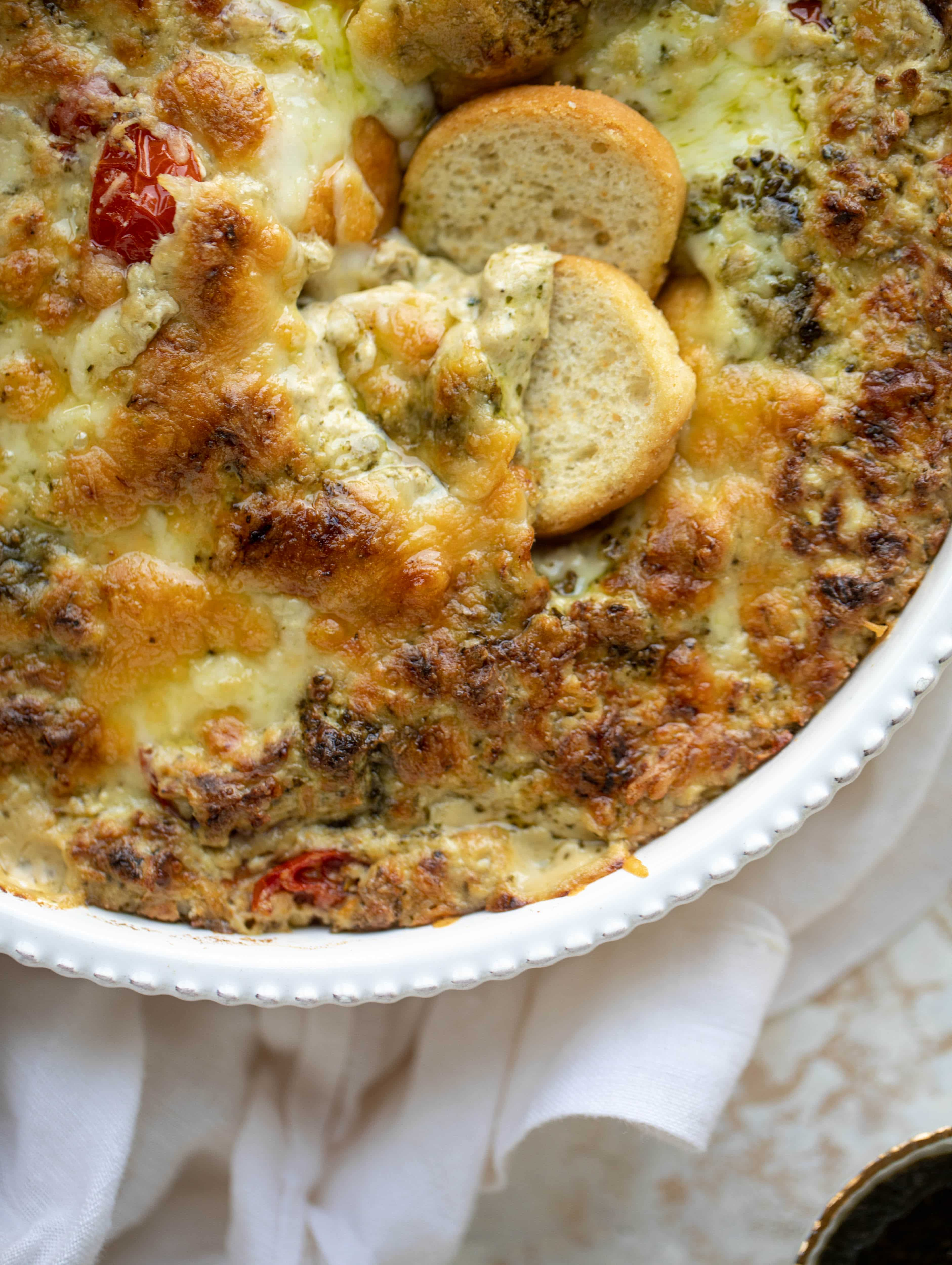 This cheesy pesto chicken dip is a great way to use up your end-of-summer herbs! Lots of delicious smoky flavor and tons of bubbly cheese.