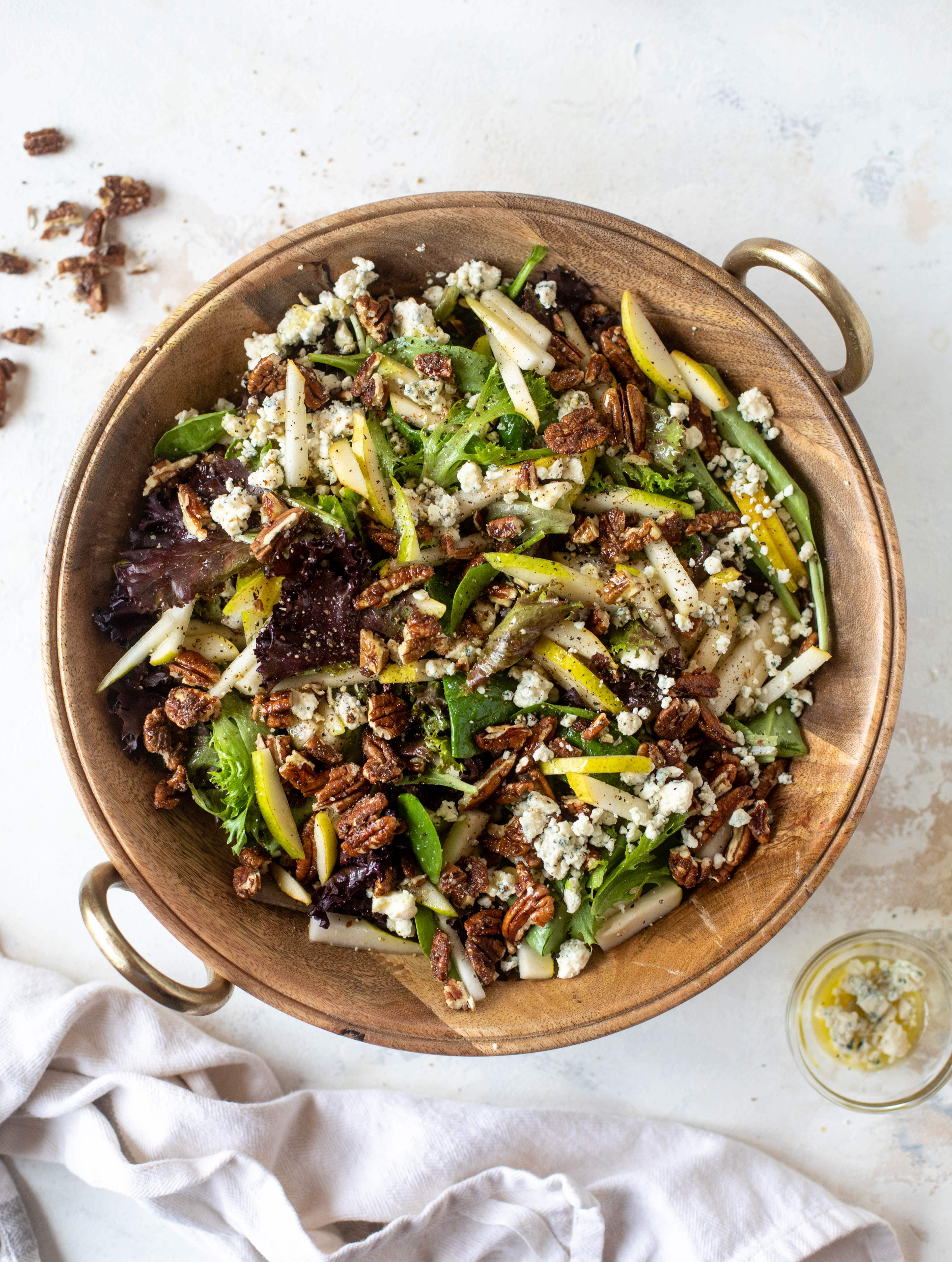 This pear gorgonzola is the perfect simple greens salad for the holiday and winter season! Topped with sweet and spicy pecans and champagne vinaigrette!