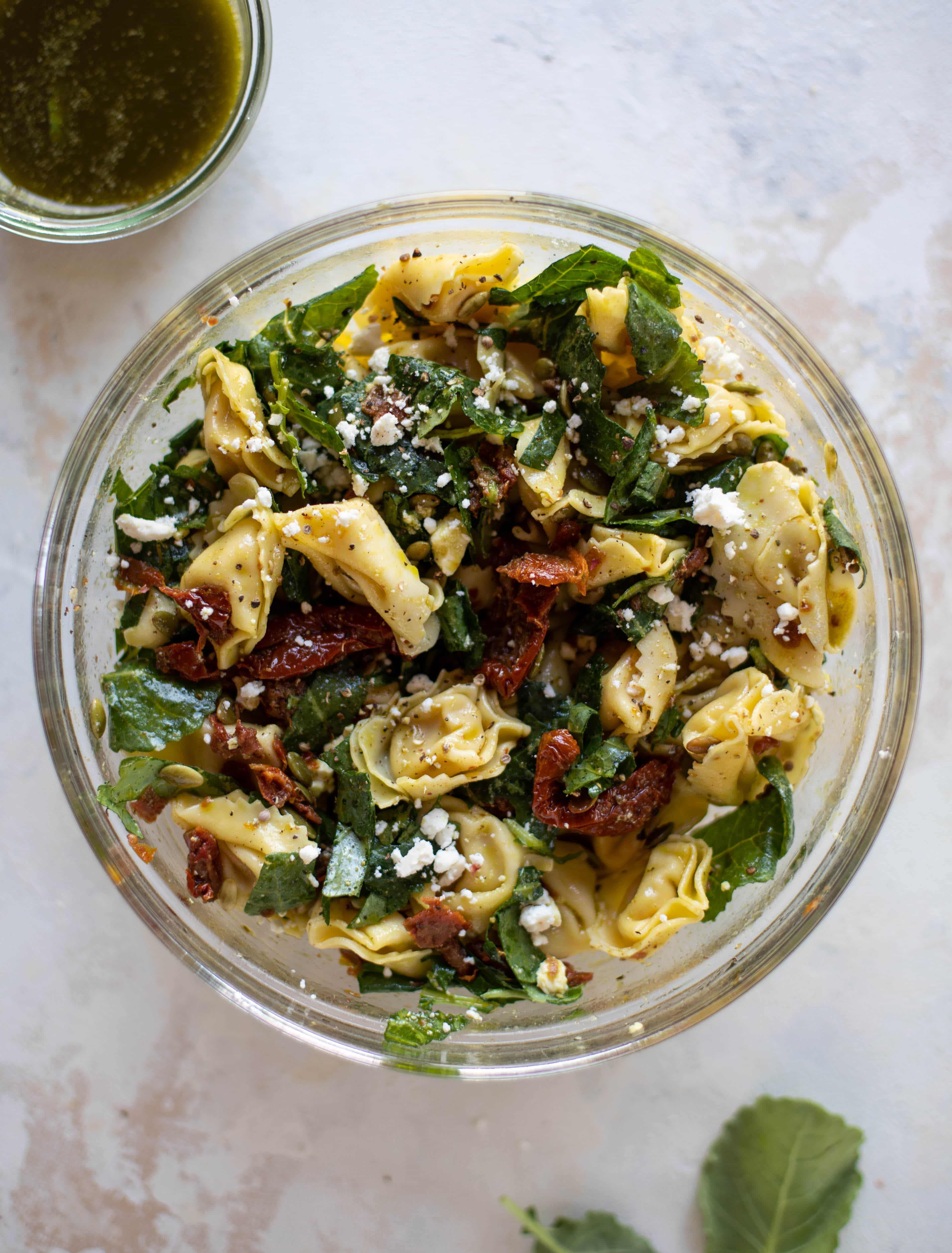 This cilantro lime tortellini salad is loaded with flavor! Served warm or cold, it has pepitas, sun dried tomatoes and crumbled feta. It's ridiculously good!
