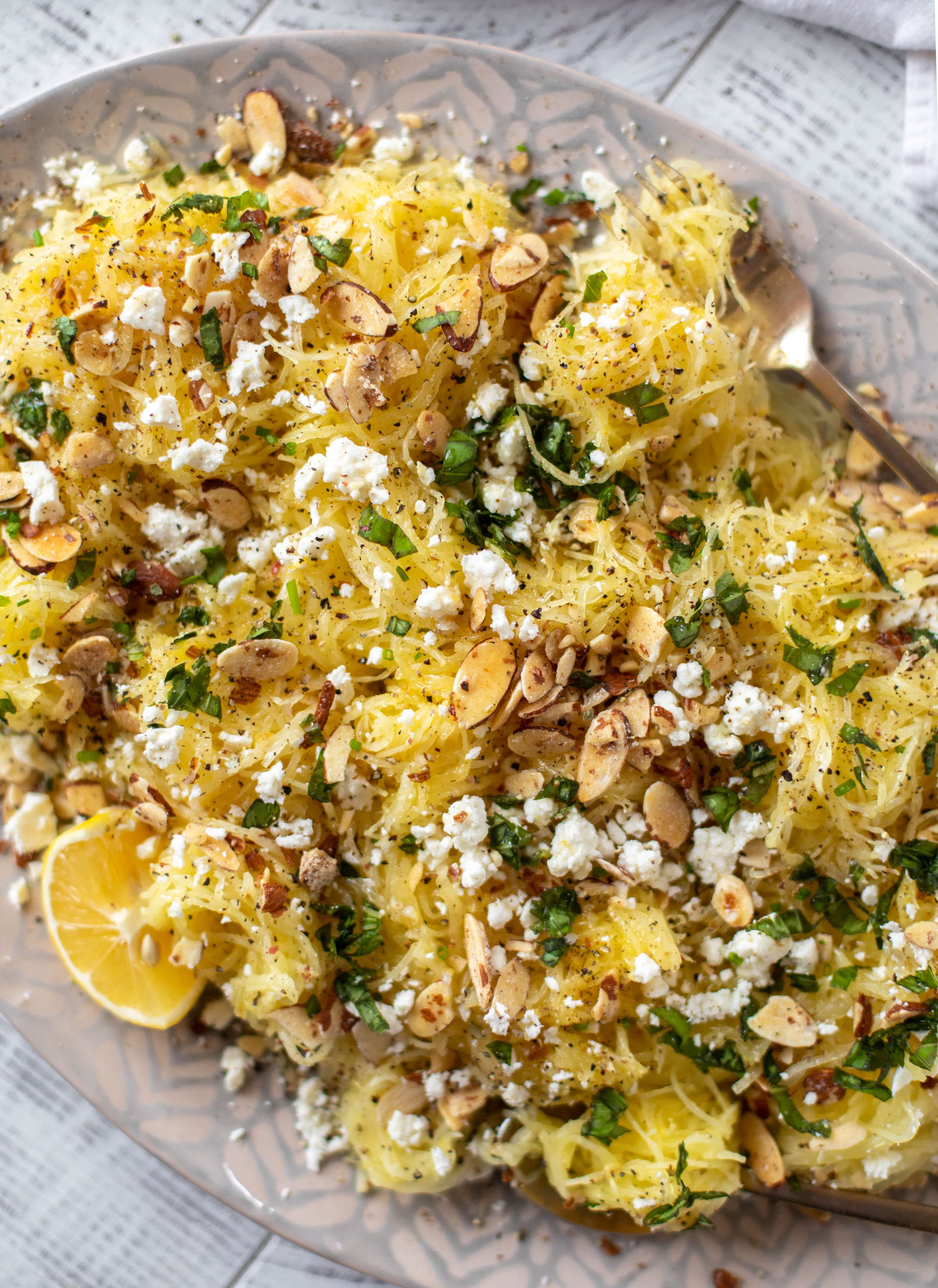 This lemon spaghetti squash is tossed in a lemon garlic butter and topped with feta, sliced toasted almonds and fresh herbs. It's delicious!