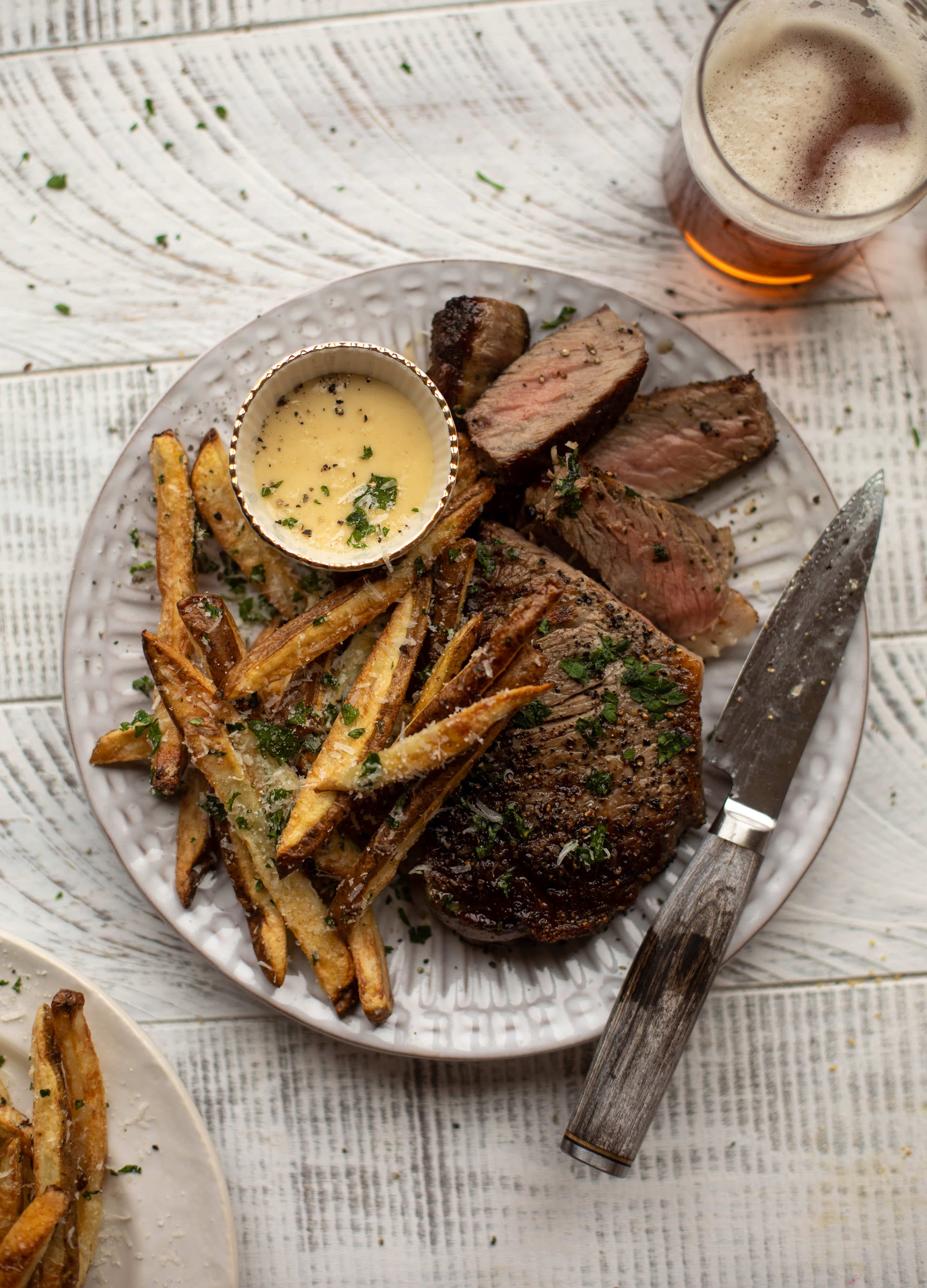This is our favorite steak frites! Seared skillet steak and crispy fries made in the air fryer, topped with truffle salt, parmesan and herbs!