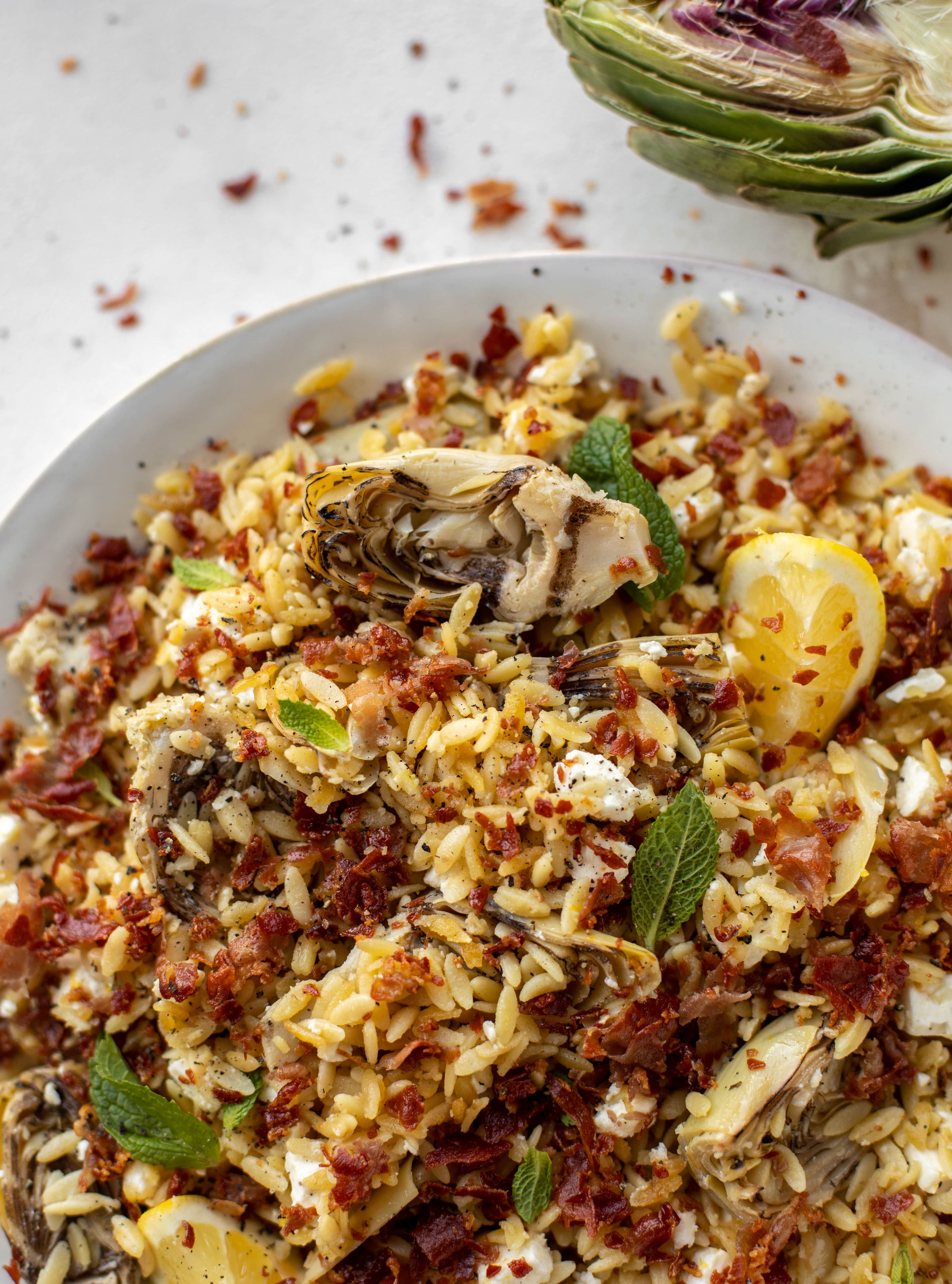 This crispy orzo is a wonderful spring dish. Artichoke hearts, lemon, goat cheese and herbs all topped with a sprinkling of crunchy prosciutto.