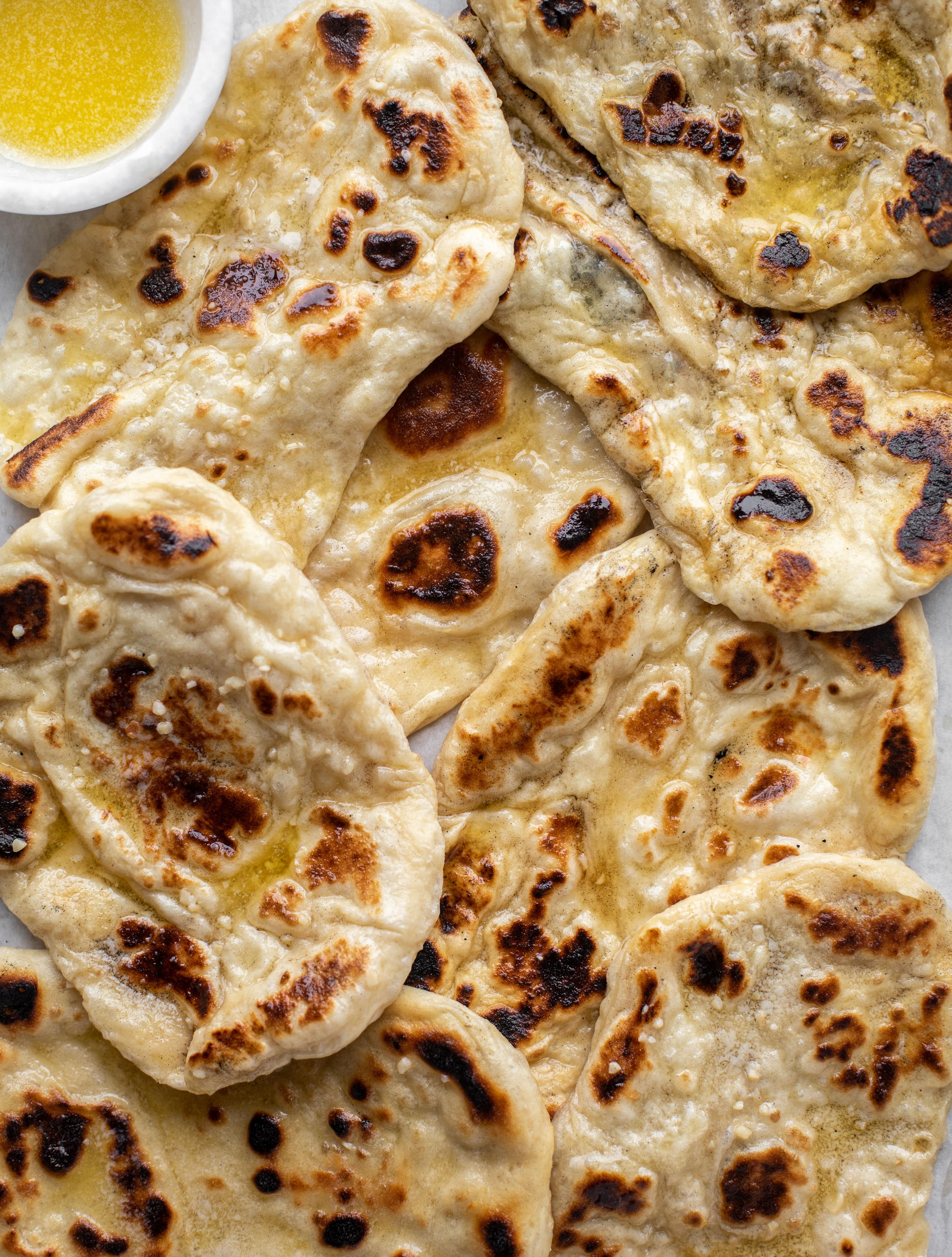 This garlic butter naan bread recipe is divine! It uses baking powder and baking soda instead of yeast and is drenched with garlic butter. So delicious!