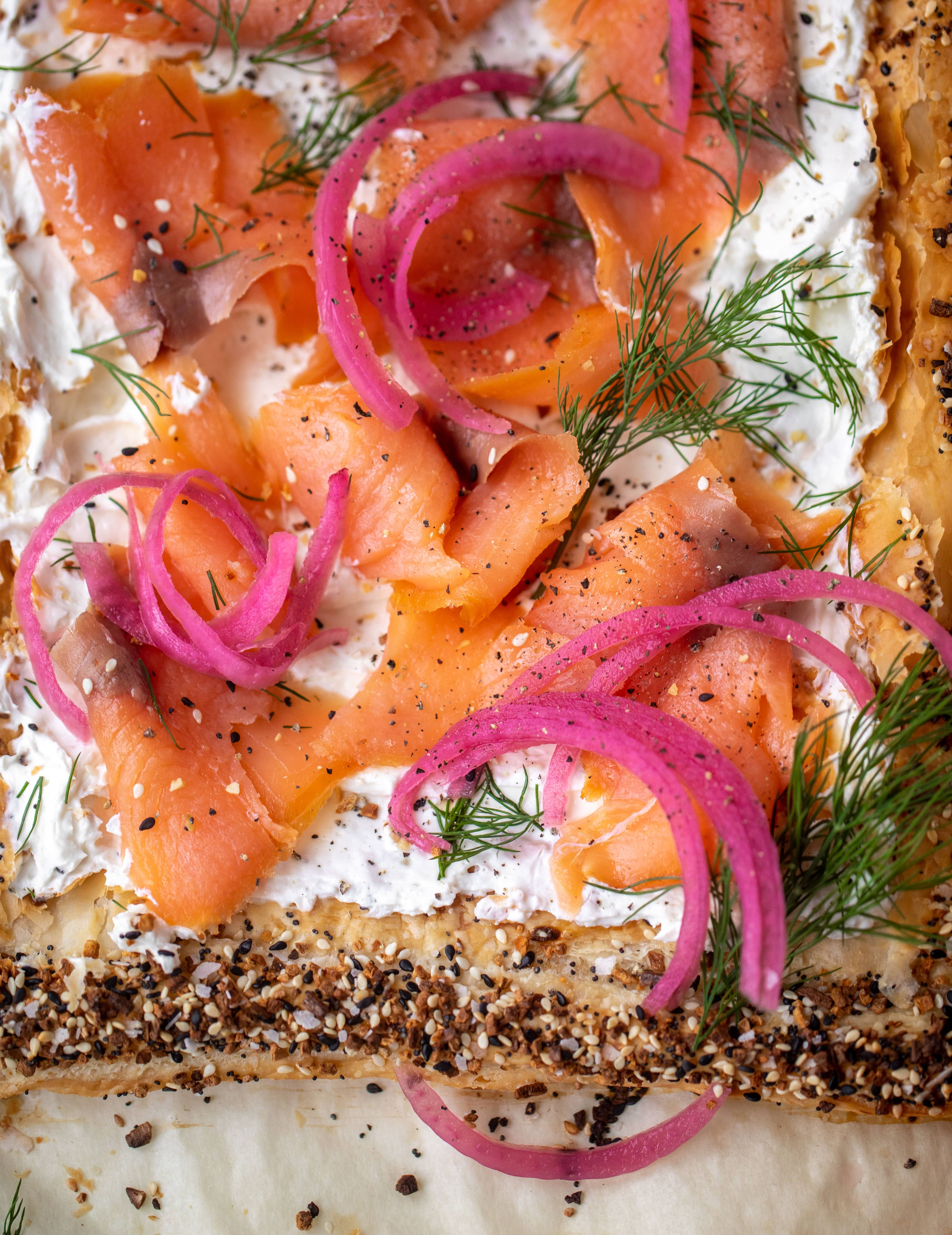 This everything smoked salmon tart is perfect for brunch! Puff pastry sprinkled with everything seasoning, slathered in cream cheese and topped with salmon.