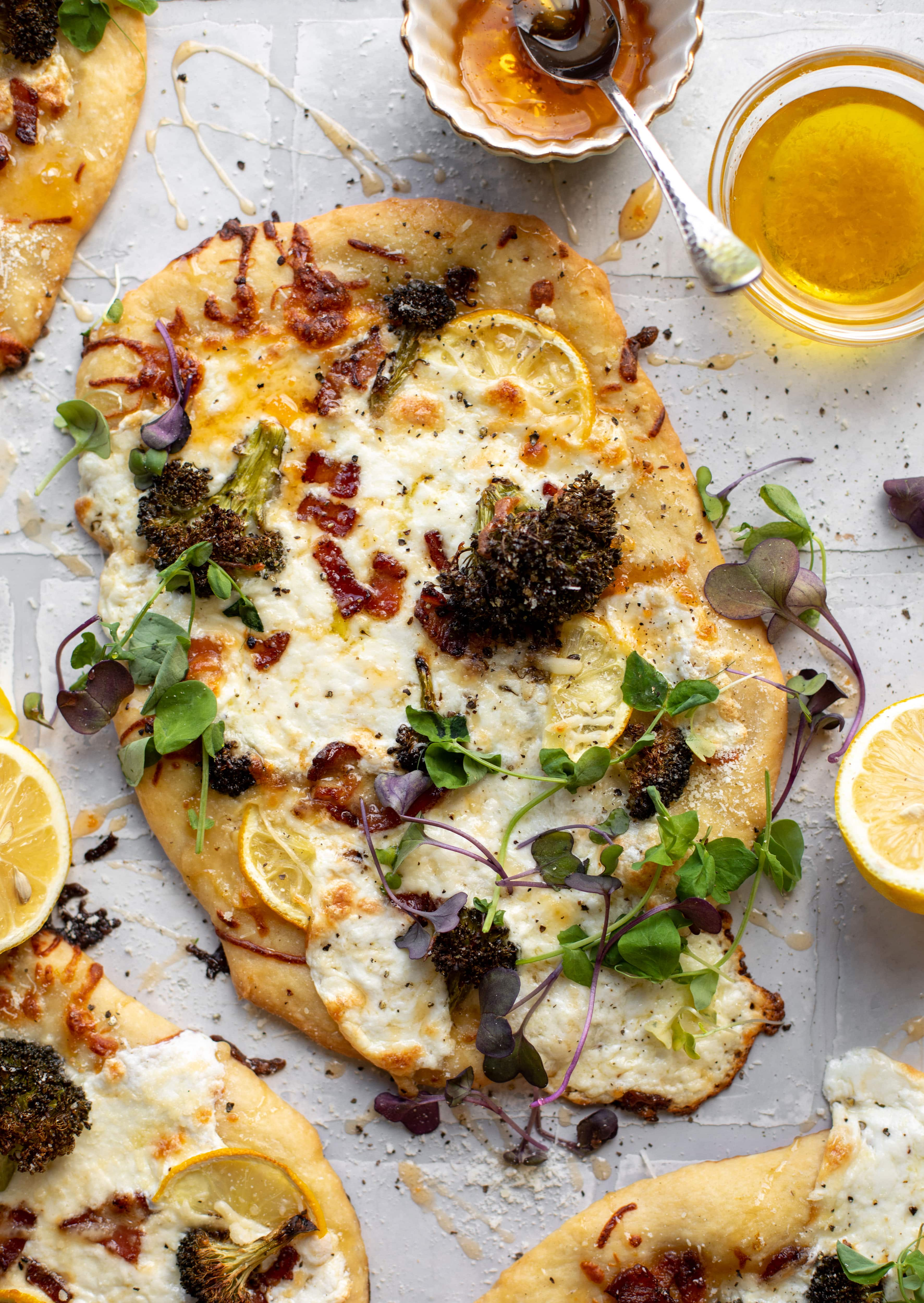 This cheesy lemon flatbread pizza is covered with burrata cheese, parmesan, roasted vegetables and hot honey. It's a flavor dream!