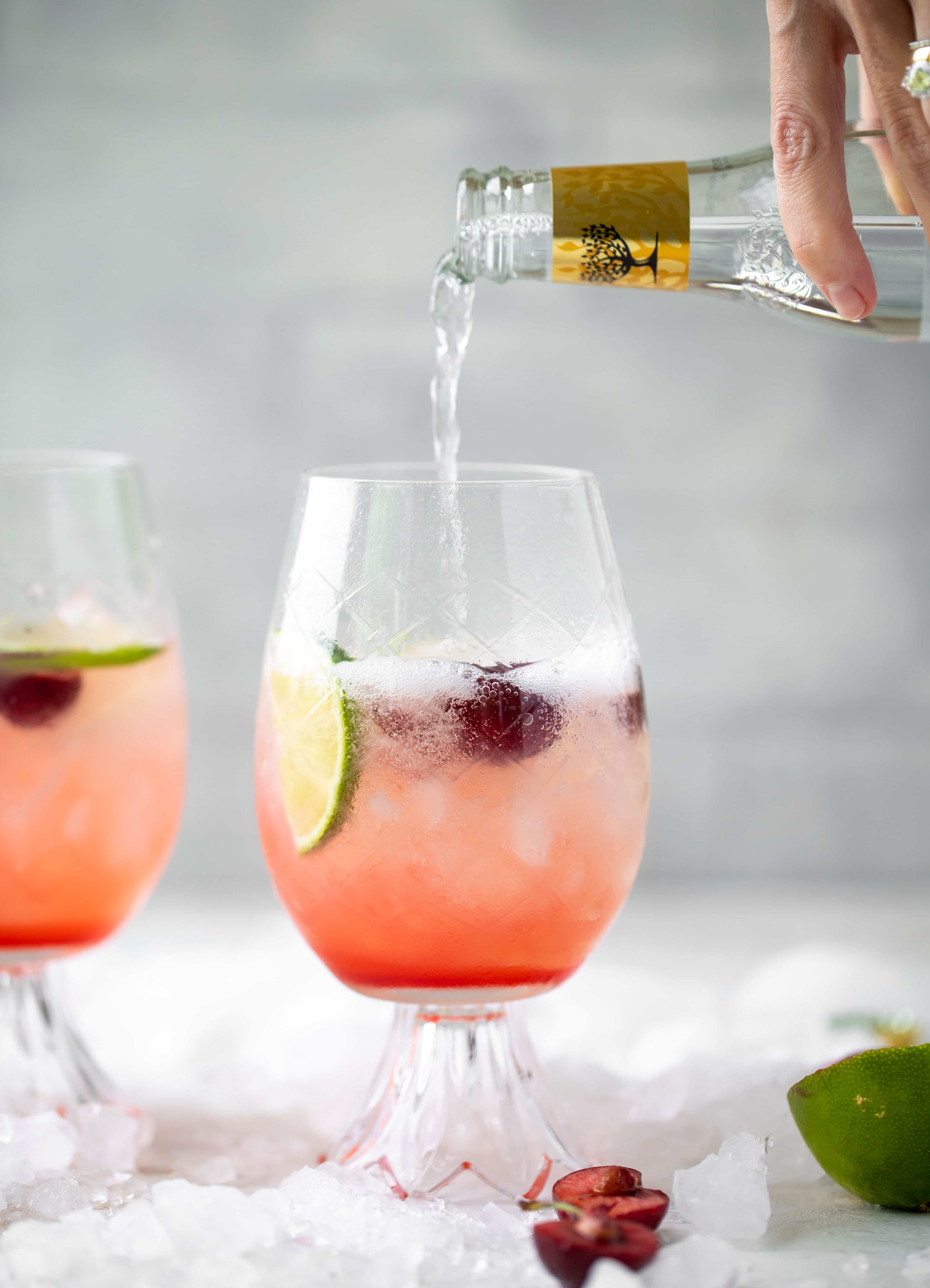 pouring tonic into cherry lime gin and tonic