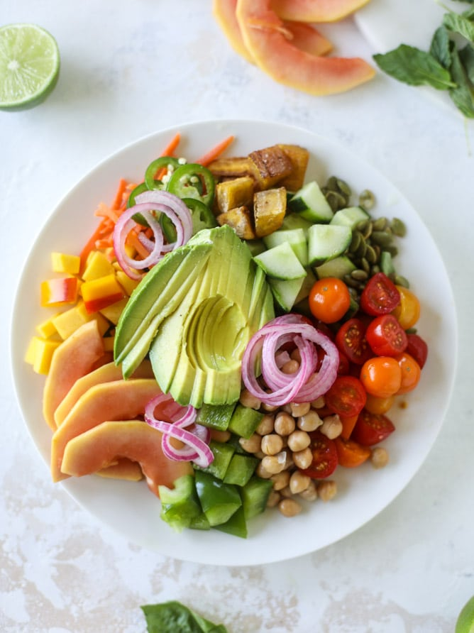 This spicy rainbow salad is chock full of gorgeous, fresh produces, chickpeas, plantains and herbs for one beautiful sight in a bowl. The rainbow salad is satisfying, filling, delicious with a touch of sweet and slightly spicy - everything you want in a meal! I howsweeteats.com #spicy #rainbow #salad