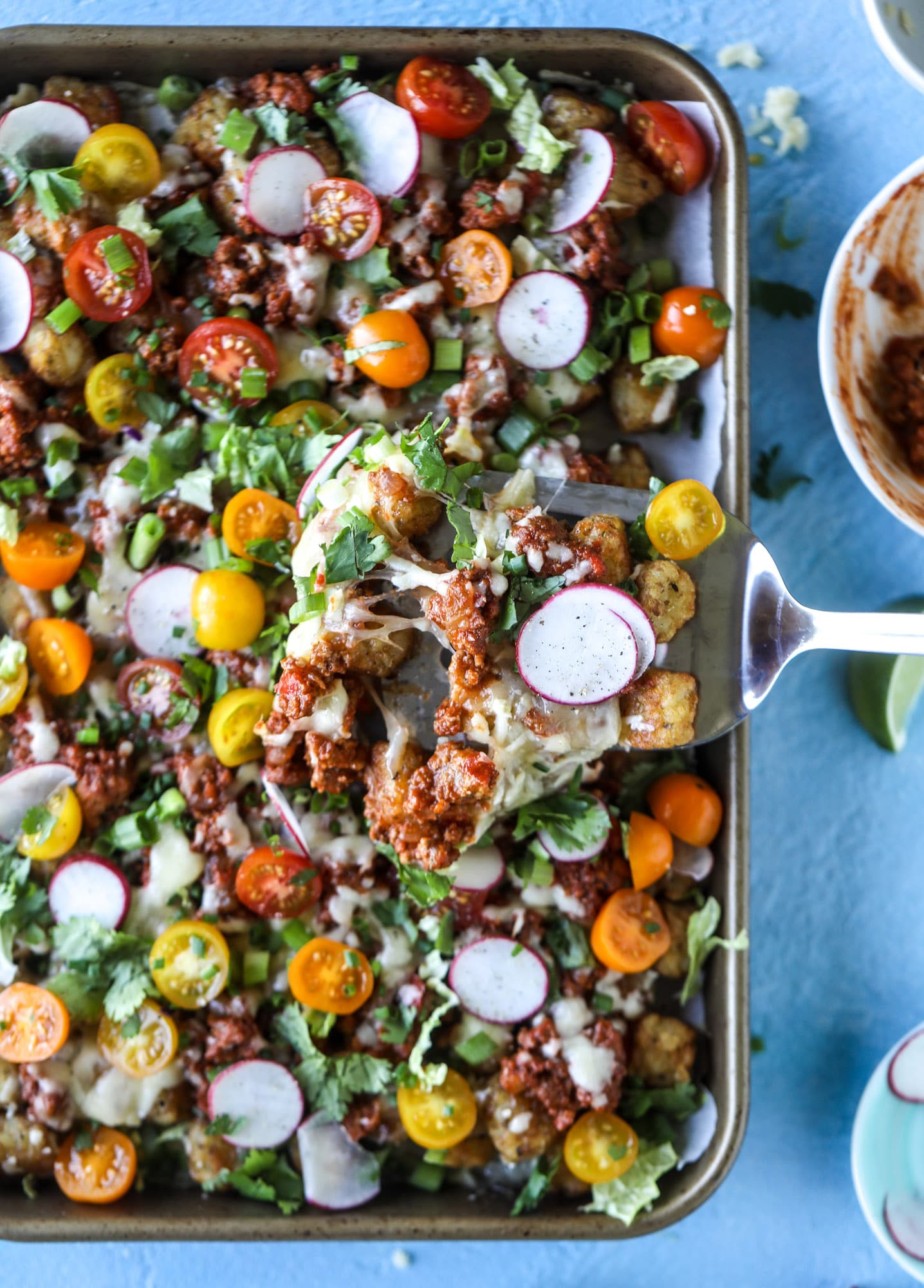 These tater tot nachos, otherwise known as totchos, are so delicious! They are cheesy and topped with a tangy, homemade sloppy joe mixture. Melted cheese, fresh tomatoes, scallions and chives come together for the best party food. I howsweeteats.com #totchos #tater #tot #nachos #sloppy #joes
