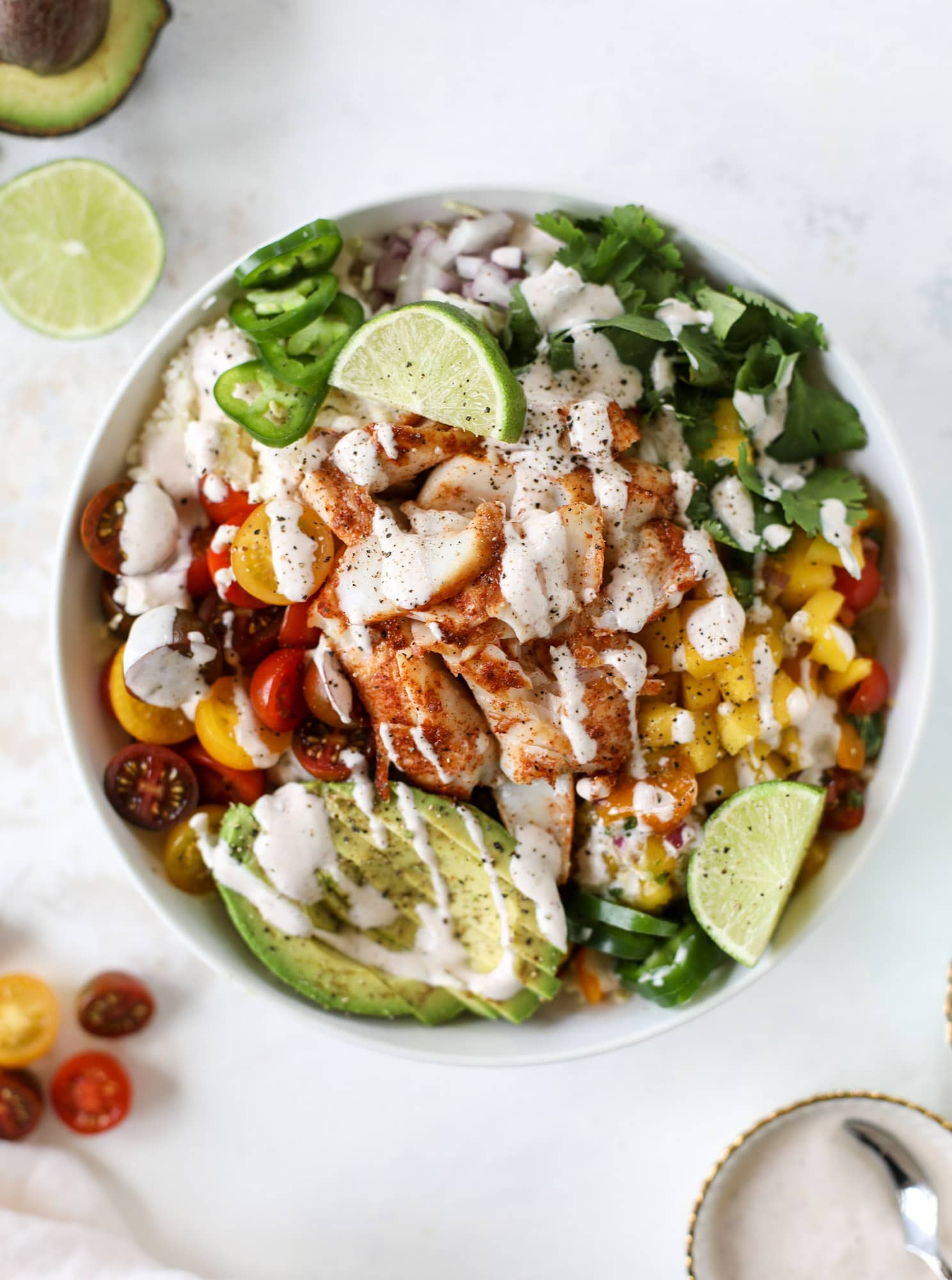 These fish taco bowls are an amazing weeknight meal idea! Napa cabbage for the base, a homemade chipotle crema, avocado, mango pico de gallo, spicy broiled white fish and lots of lime. Major flavor explosion and so easy too! I howsweeteats.com #fish #taco #bowls #spicy #healthy #dinner