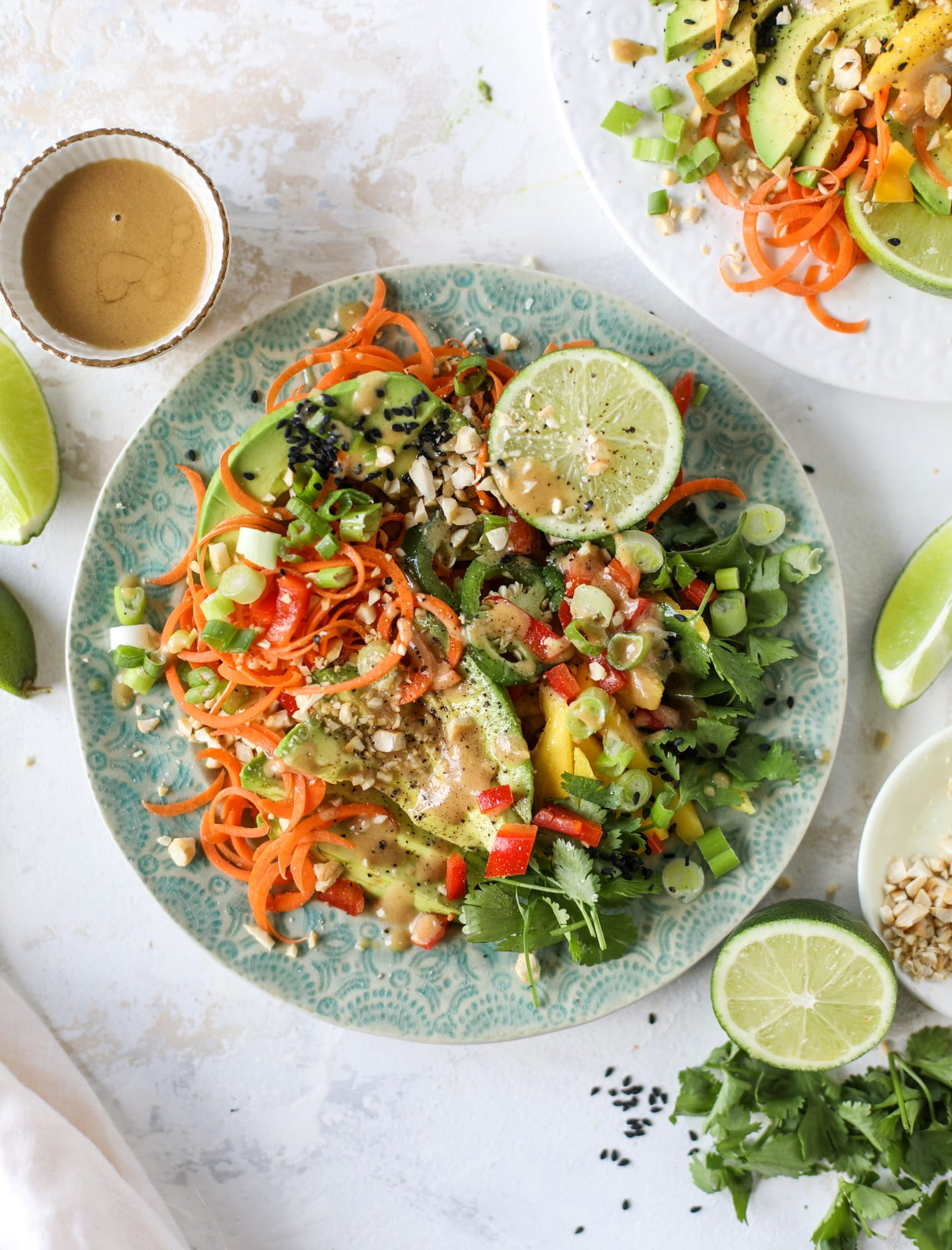 This thai avocado salad is loaded with mango, red pepper, carrots, green onions and drizzled with a peanut butter vinaigrette. It's an amazing side salad or a fabulous dinner salad - add on chickpeas or shrimp or chicken if you wish! I howsweeteats.com #thai #avocado #salad #peanutbutter #mango #lime