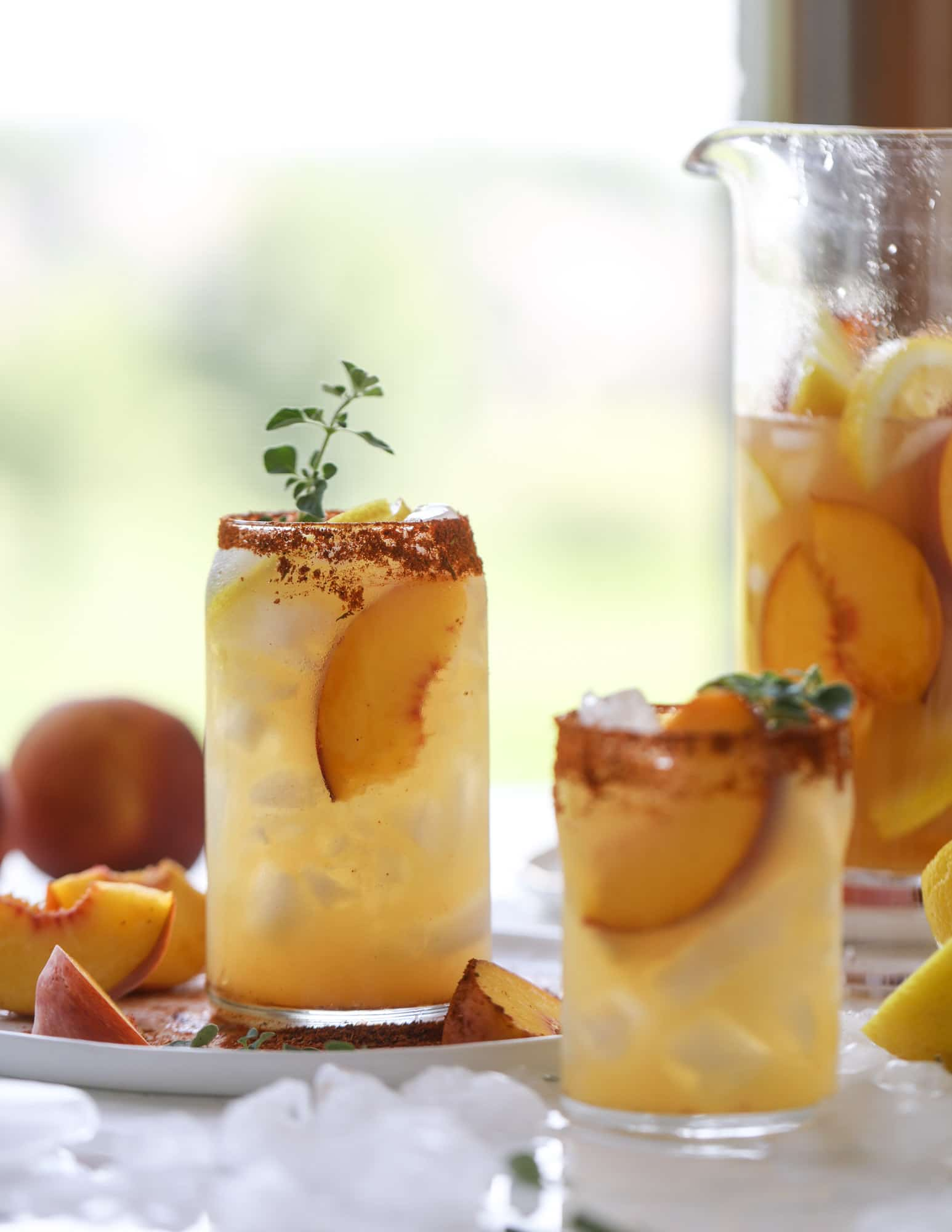 This peach lemonade is super refreshing and a bit spicy for a hot and sunny summer day. It's sweet and fresh and the rim is dipped in a cajun seasoning, bringing the best bite of heat to this perfect summer drink. So fresh! I howsweeteats.com #peach #lemonade #cajun  #summer #mocktail #lemon #drink
