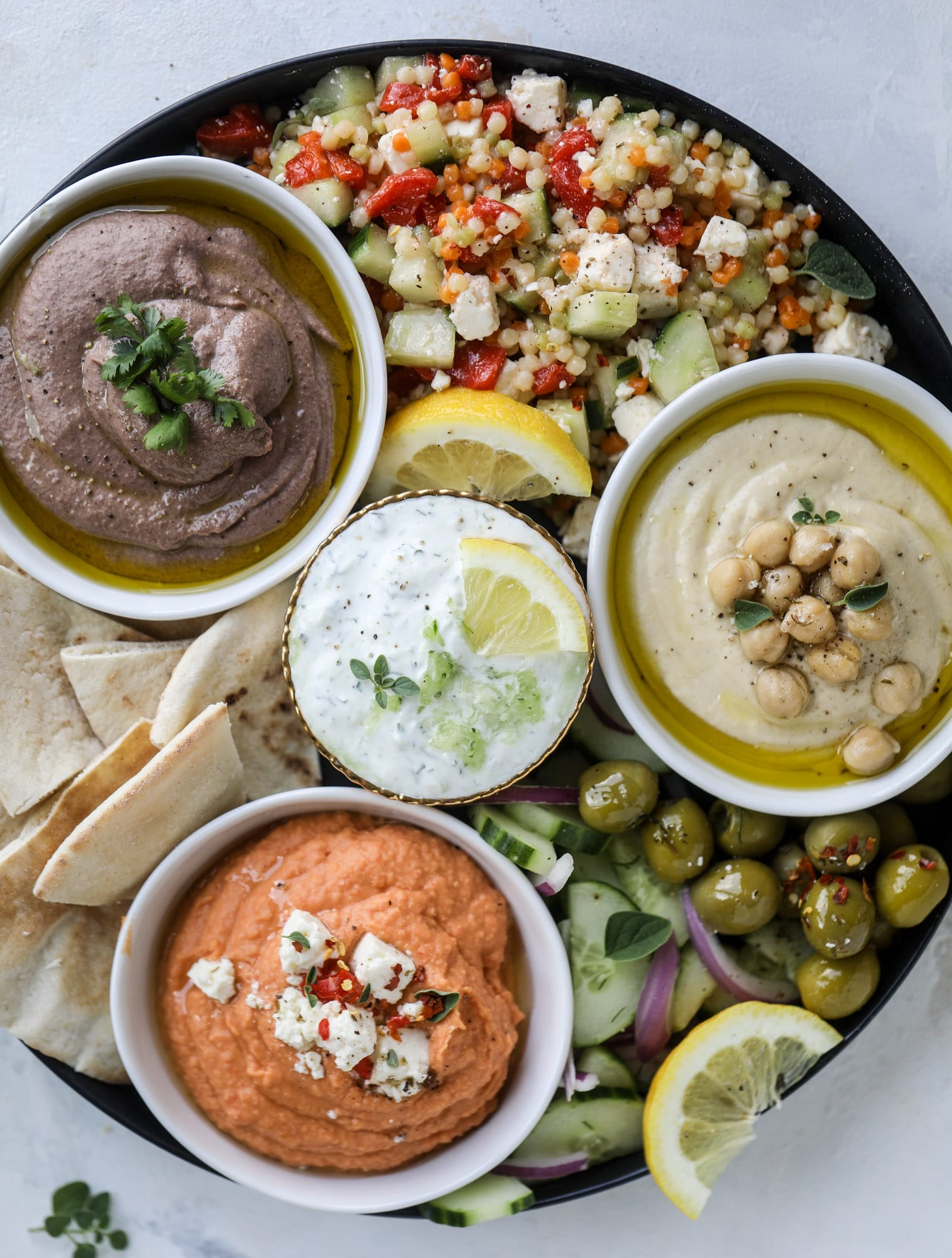 Here you can find out how to make the perfect hummus platter! This trio includes caramelized onion hummus, smoky black bean hummus and roasted red pepper white bean hummus, along with a couscous salad and quick tzatziki! I howsweeteats.com #hummus #platter #appetizer #snack #chickpeas #healthy #blackbeans #yogurt #tzatziki