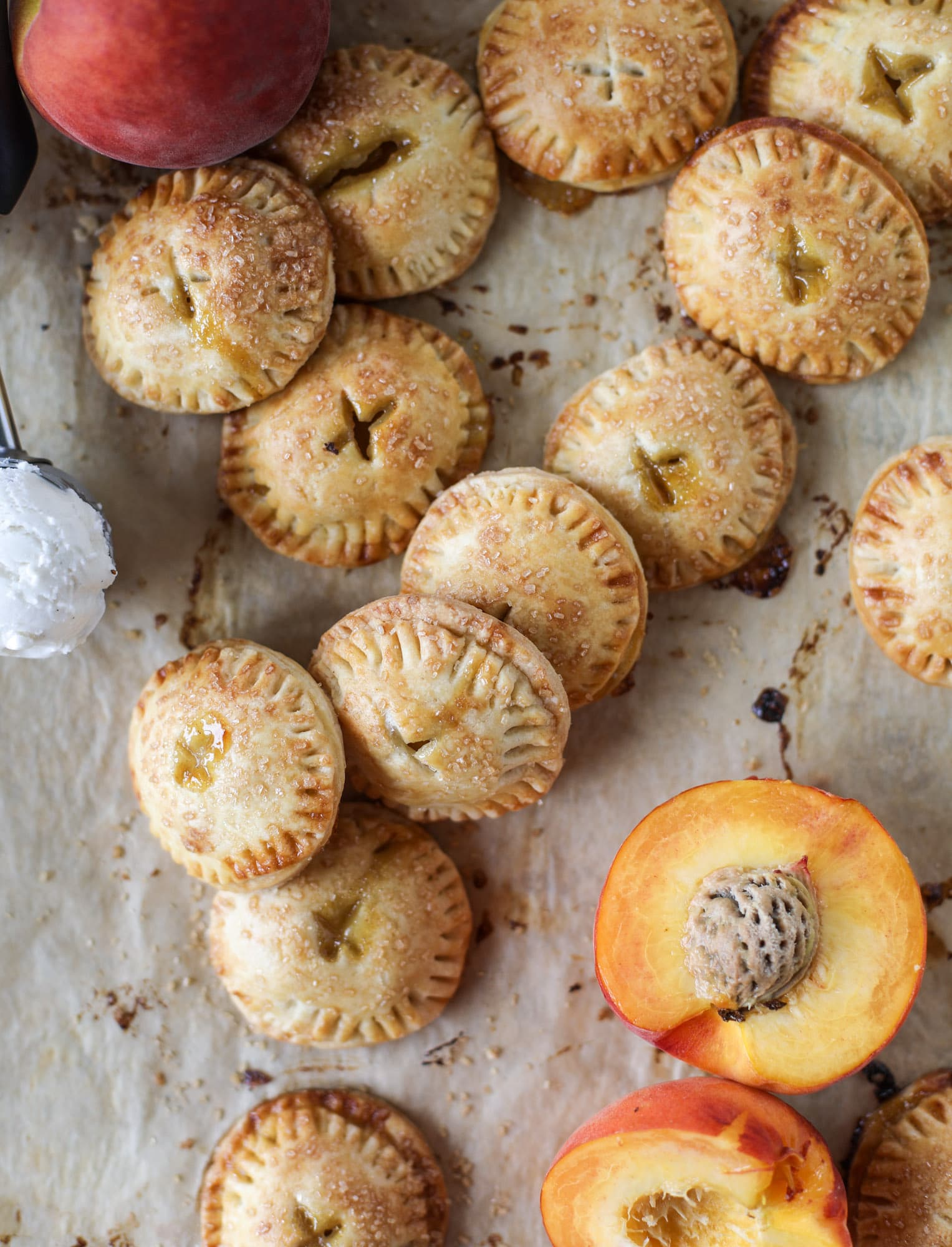 These little peach hand pies are super easy to make and oh-so delicious for summer! A warm and syrupy homemade peach filling made with brown sugar and bourbon, stuck inside a flakey all-butter crust and sprinkled with coarse sugar. SO GOOD. I howsweeteats.com #peach #hand #pies #mini #dessert #summer