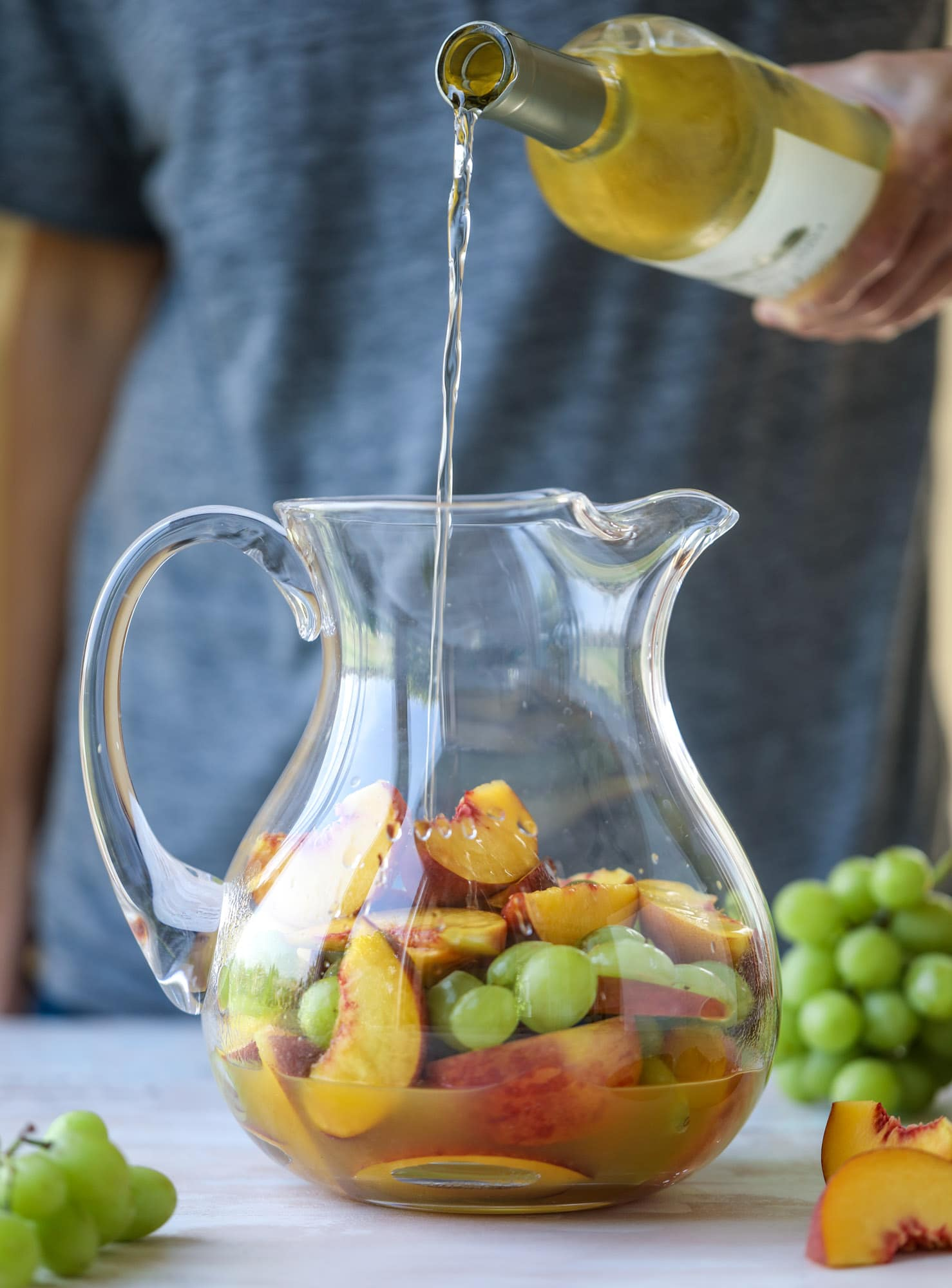 This pinot grigio sangria is absolutely perfect for summer, complete with peach nectar, fresh and frozen peach slices, brandy and bubbles! Frozen green grapes add some chill without watering down the drink. It's perfect! I howsweeteats.com #pinot #grigio #peach #sangria #cocktails #punch #summer #wine