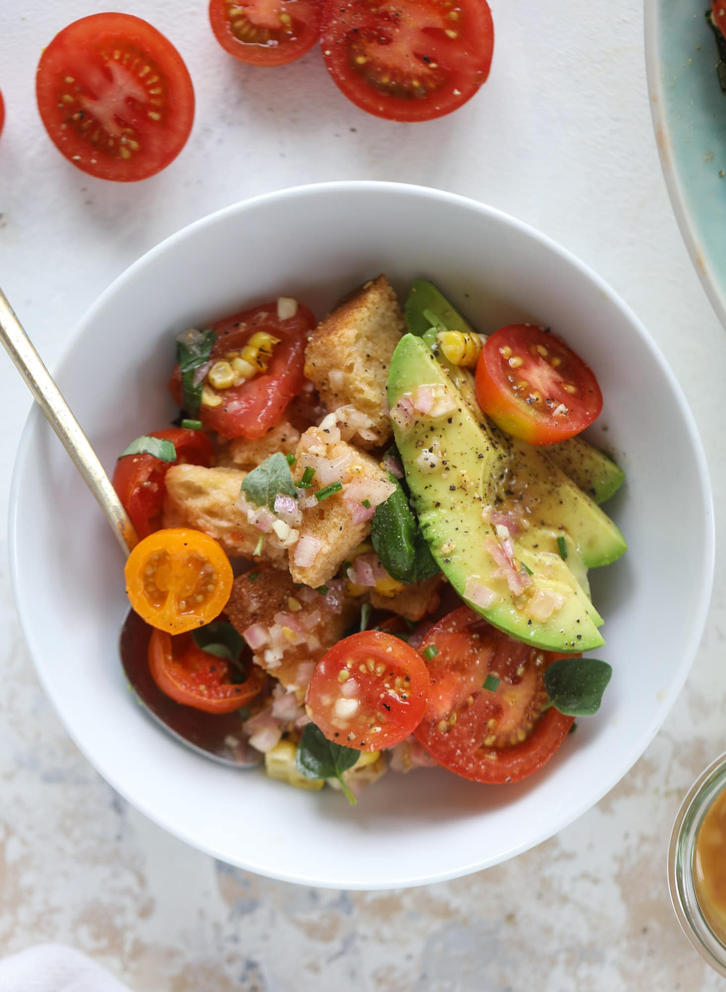 This is the perfect tomato panzanella salad! It's full of juicy, bursting, sweet tomatoes, toasted sourdough bread cubes, fresh herbs, grilled corn, sliced avocado and an incredible homemade dressing that blankets everything in deliciousness. SO good. I howsweeteats.com #panzanella #salad #tomato #basil #summer #corn #avocado #healthy #recipes