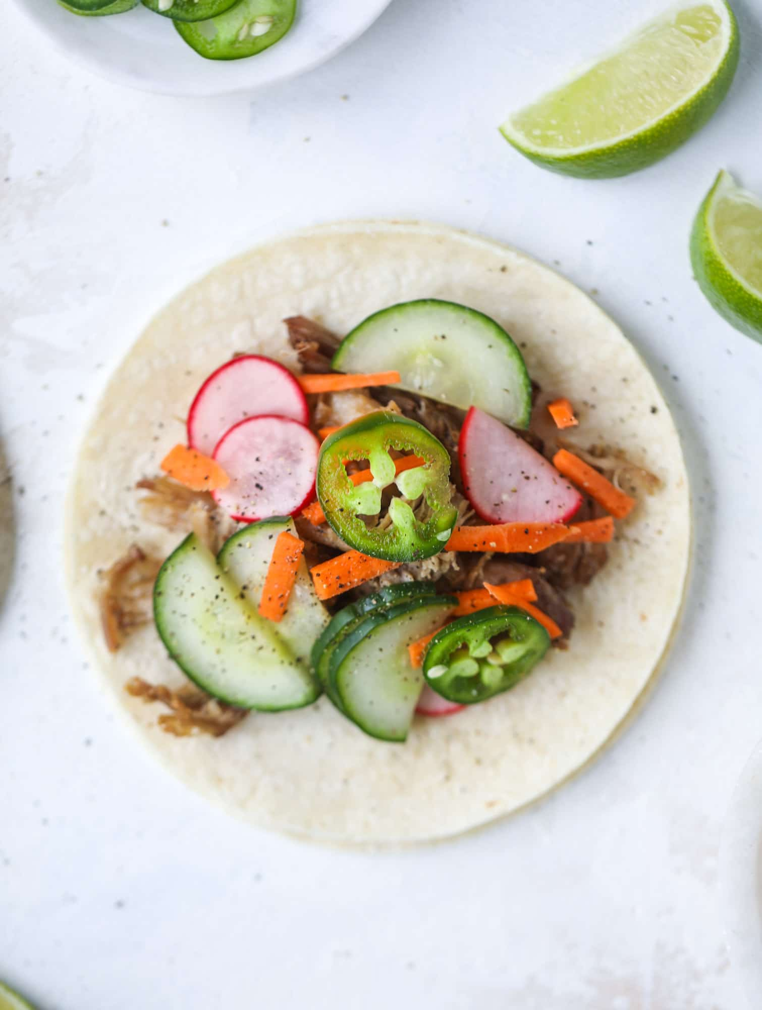These bahn mi tacos are the perfect twist on the classic sandwich! Juicy pulled pork, pickled veggies, a tangy crema and loads of flavor. Bahn mi tacos are a delish weeknight meal or also work great if you have pork leftovers! I howsweeteats.com #bahn #mi #tacos #pork #dinner