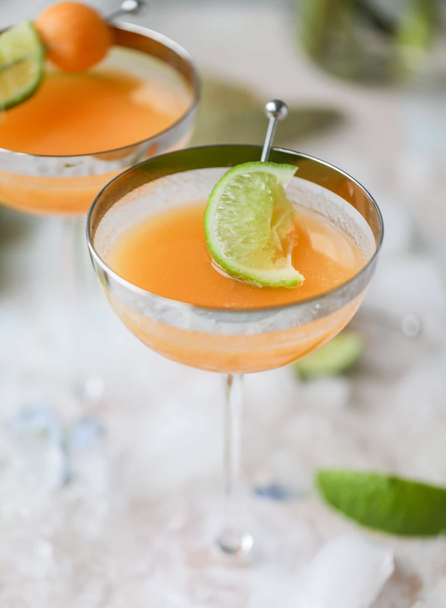 This cantaloupe daiquiri is the perfect way to celebrate summer! Freshly juiced melon, lime juice, rum and maraschino cherries - it's refreshing and cool and a fantastic cocktail to have during happy hour! Isn't the color amazing too?! I howsweeteats.com #cantaloupe #cocktail #daiquiri #lime #rum #summer