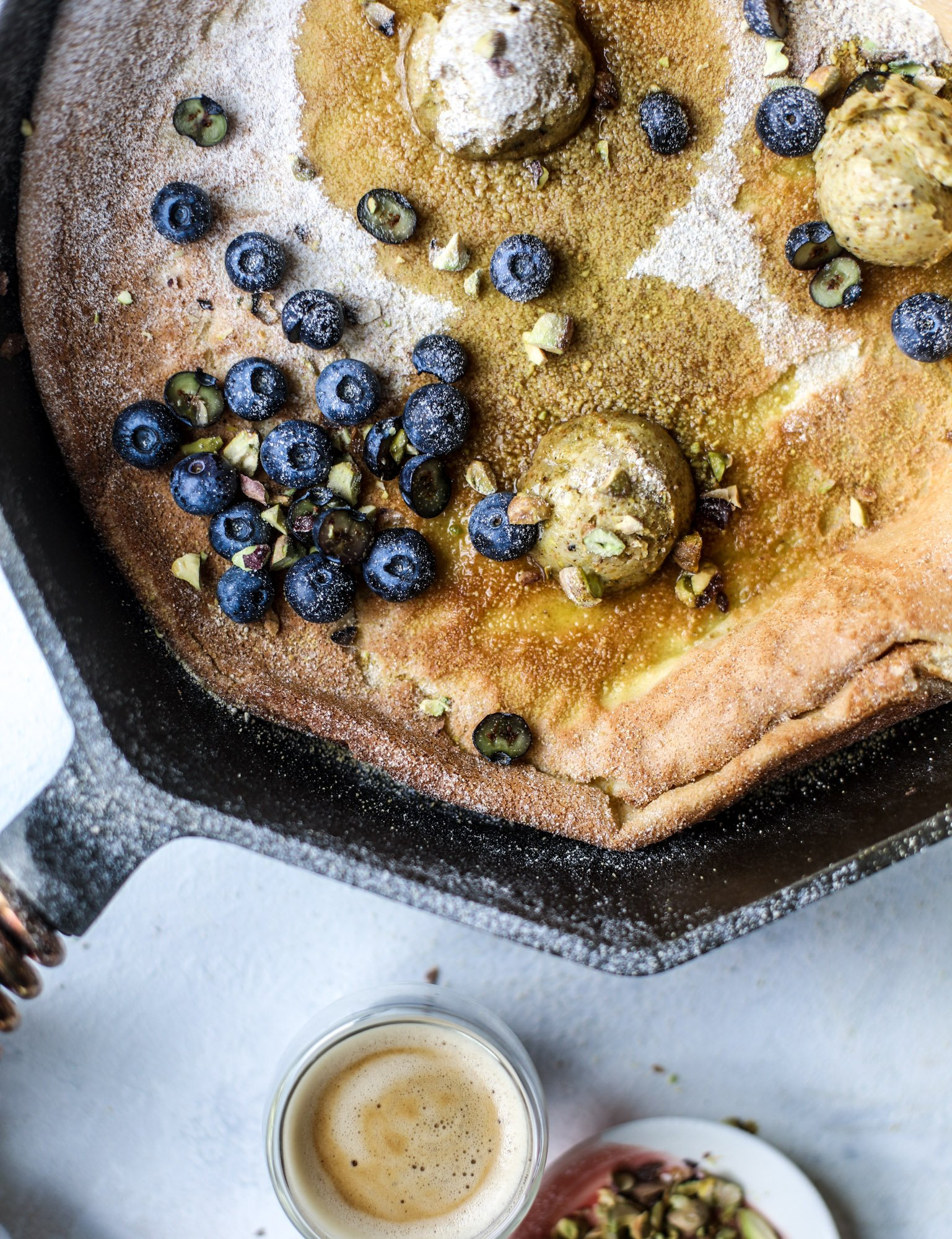 This incredible dutch baby recipe is fluffy and light and perfect for breakfast! It's sprinkled with pistachio sugar and served with pistachio butter and fresh blueberries. It's super easy, simple and always a hit! I howsweeteats.com #dutch #baby #pistachio #blueberry #breakfast