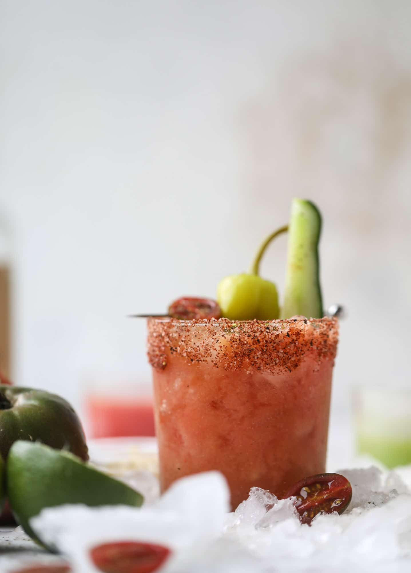 This bloody mary recipe is made with fresh heirloom tomatoes - the gems of summer! The colors swirl together to create a stunning drinking that is loaded with smoky, spicy flavor. Top with your favorite snacks foe the perfect brunch! I howsweeteats.com #bloody #mary #recipe #best #heirloom #tomatoes #cocktail