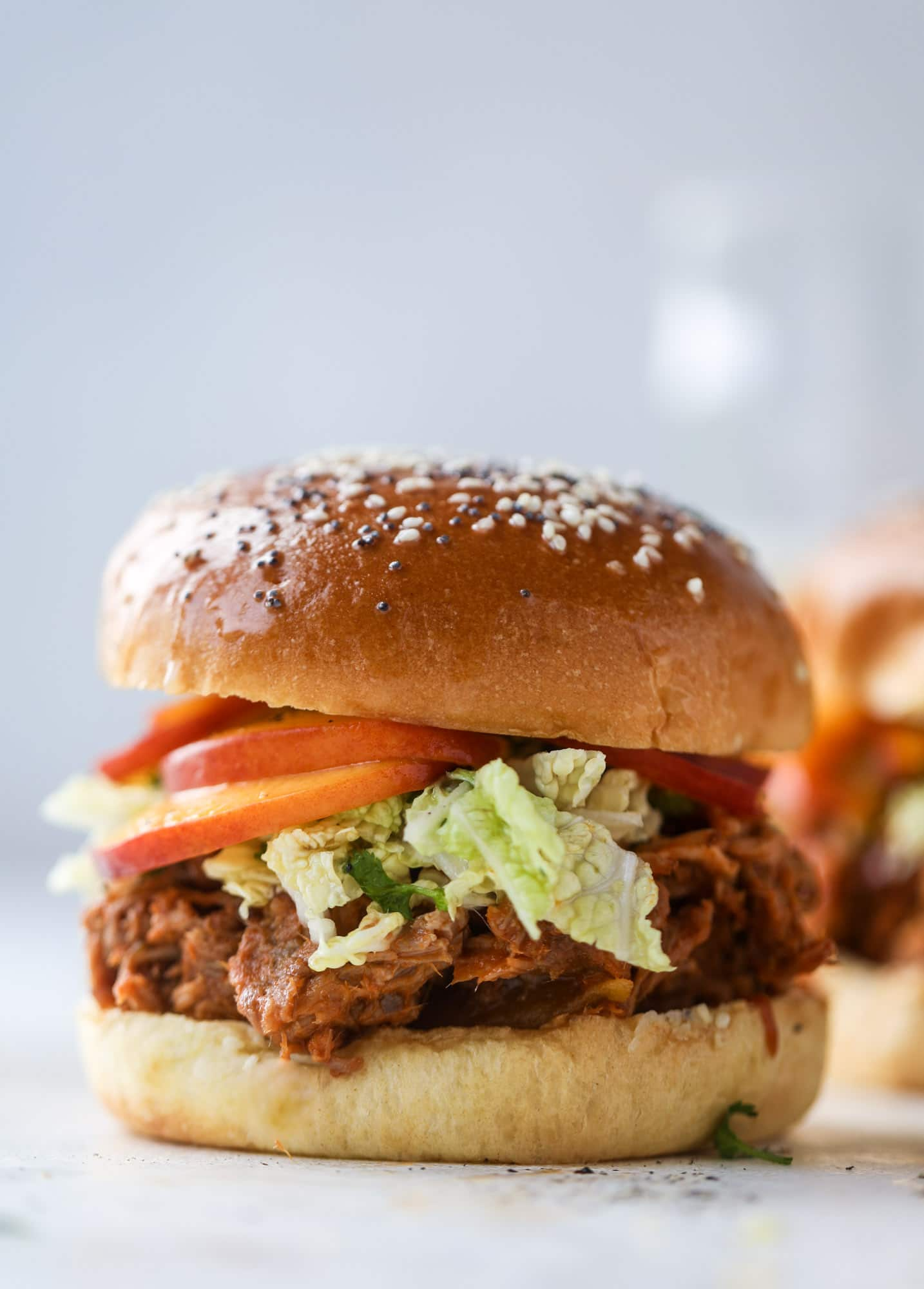 This chipotle pulled pork sandwich is spicy, sweet and saucy. Throw it on a bun or a plate and top it with the most delicious quick pickled peaches and napa cabbage slaw. Flavor and texture make this sandwich incredible! I howsweeteats.com #pulled #pork #chipotle #pickled #peaches #slaw #sandwiches #slow #cooker