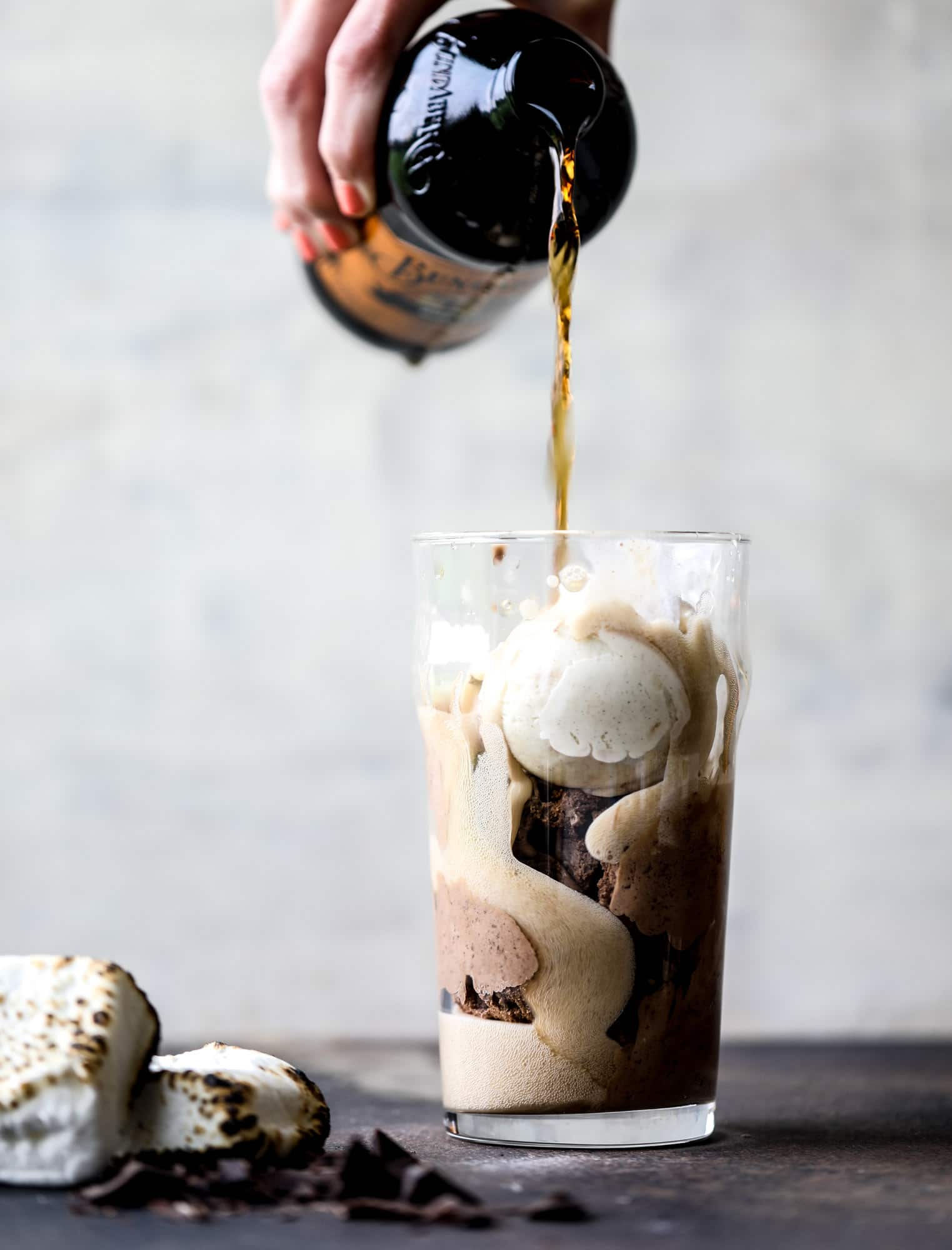 This is the most perfect root beer float, complete with both chocolate and vanilla ice creams. Topped with a smoky s'more, a chocolate fudge rim and a sprinkle of graham cracker crumbs take this super fun drink over the top! I howsweeteats.com #root #beer #float #summer #s'mores #drinks