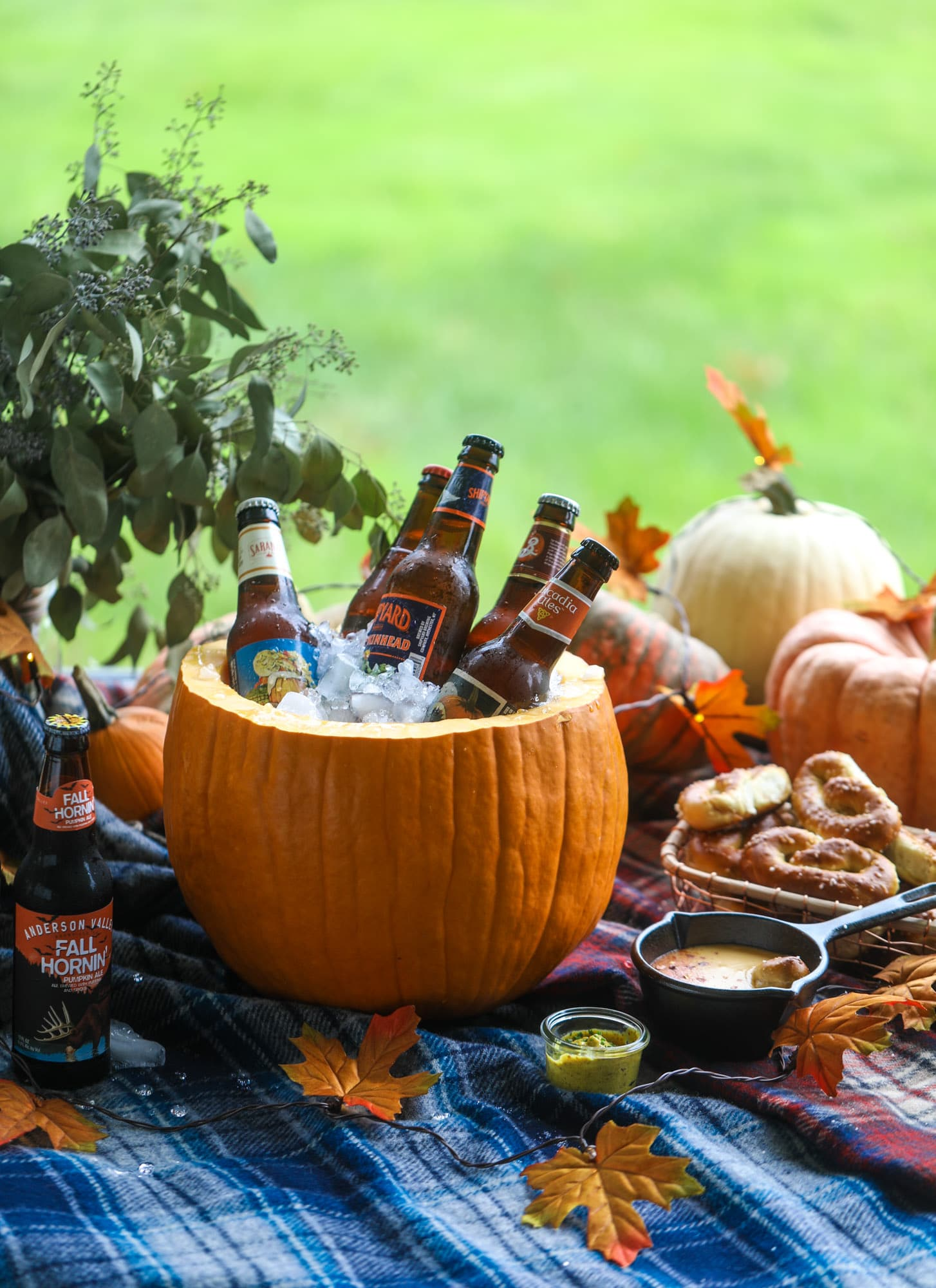 This is the cutest way ever to serve the best pumpkin beer! If you do a pumpkin beer party of a pumpkin beer tasting, this pumpkin cooler is an adorable (and easy!) way to make things festive. Kick it up with a hot pretzel bar and lots of dipping sauce too! I howsweeteats.com #pumpkin #beer #cooler #softpretzel #fall #cheese
