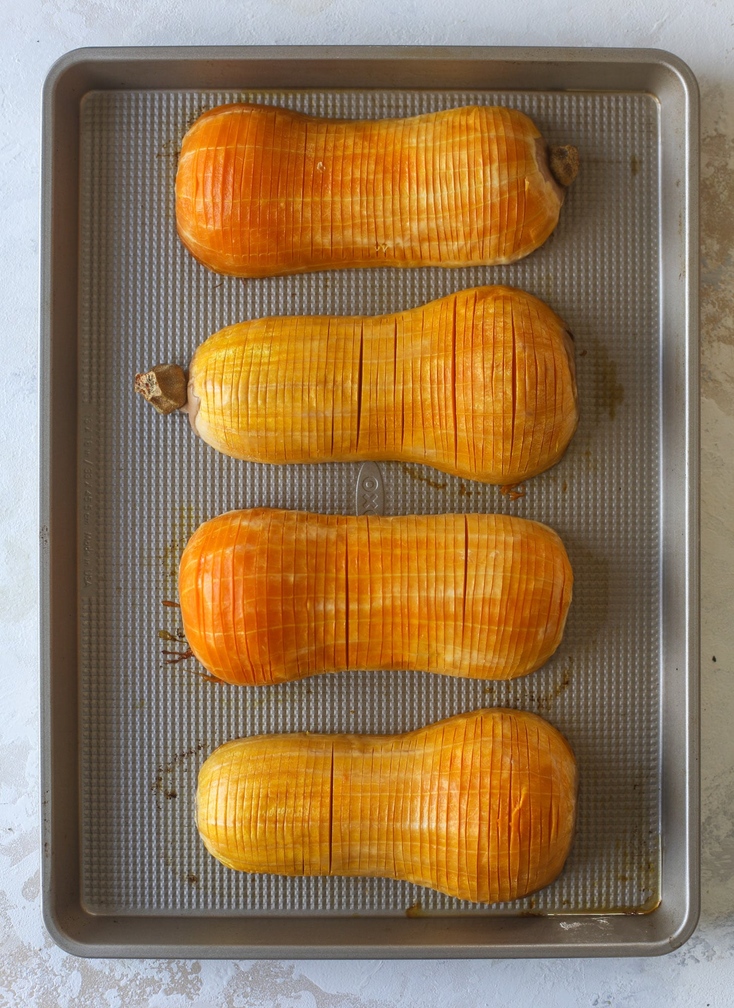 This hasselback butternut squash is perfect for Thanksgiving - and you can easily make it two ways! We have a maple pecan hassleback butternut squash and a brown butter sage hasselback butternut squash. Delicious! I howsweeteats.com #hasselback #butternutsquash