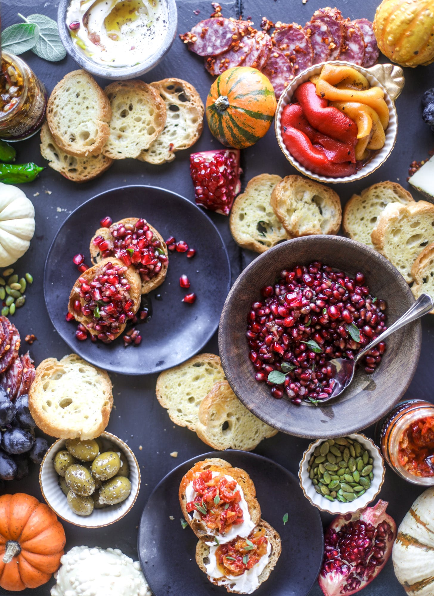 This is the perfect autumn harvest bruschetta board to feed a crowd or serve at a party! The standout is pomegranate relish with a cinnamon shallot vinaigrette, lots of toasty bread, bruschettas, cheese and olives. Everything that's delish! I howsweeteats.com #bruschetta #board